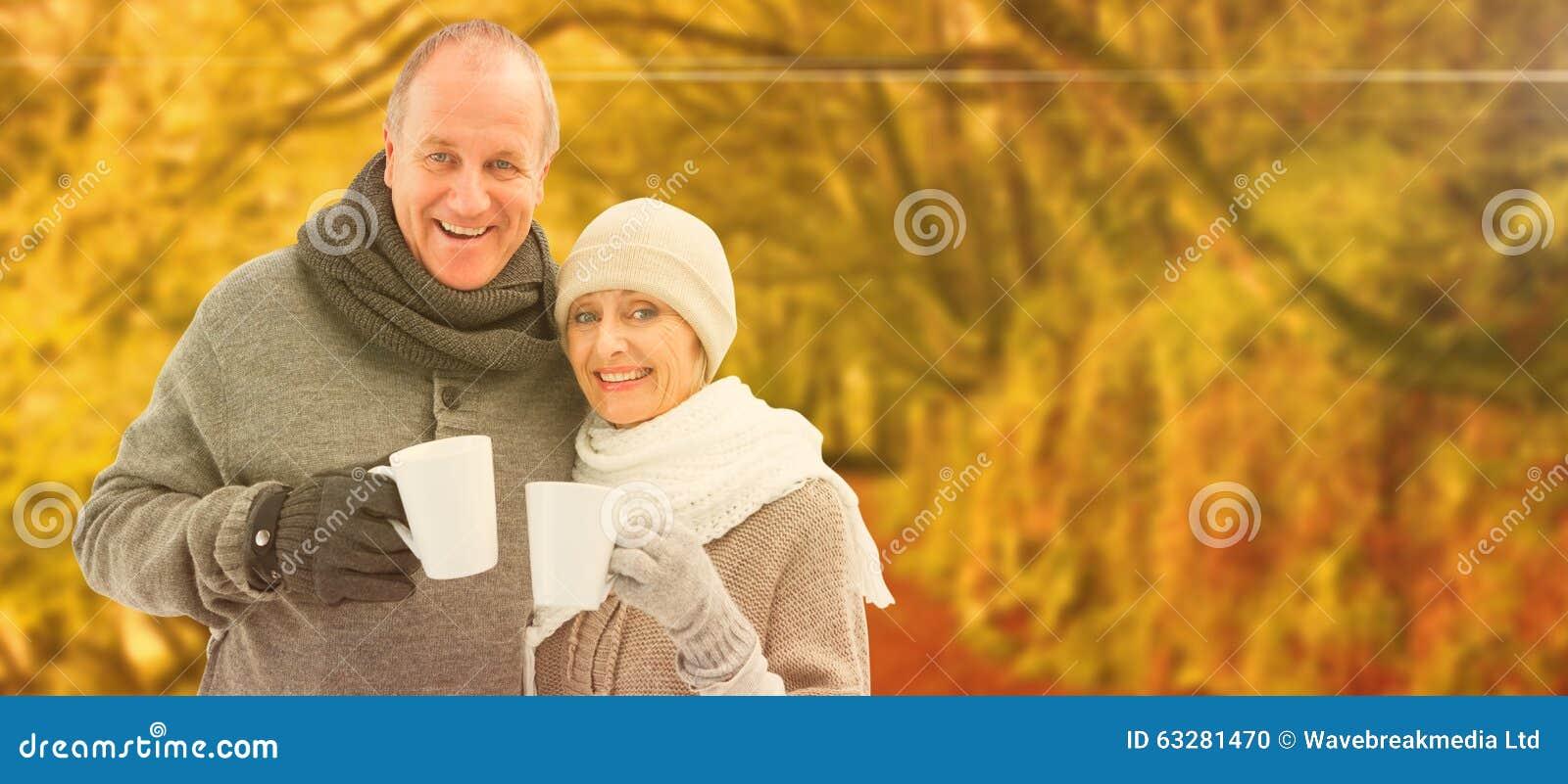 A imagem composta de pares maduros felizes no inverno veste guardar canecas