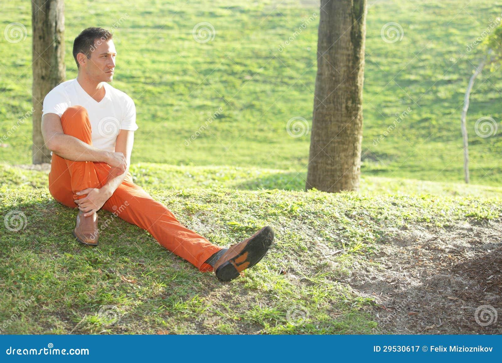 Imagem conservada em estoque de um homem que senta-se no parque