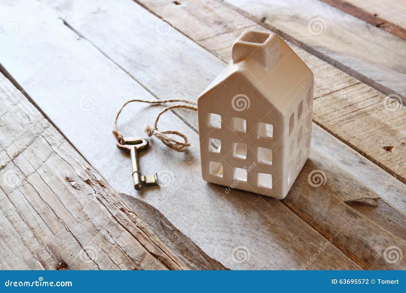 Imagem da casa diminuta pequena e chave velha sobre a tabela de madeira rústica