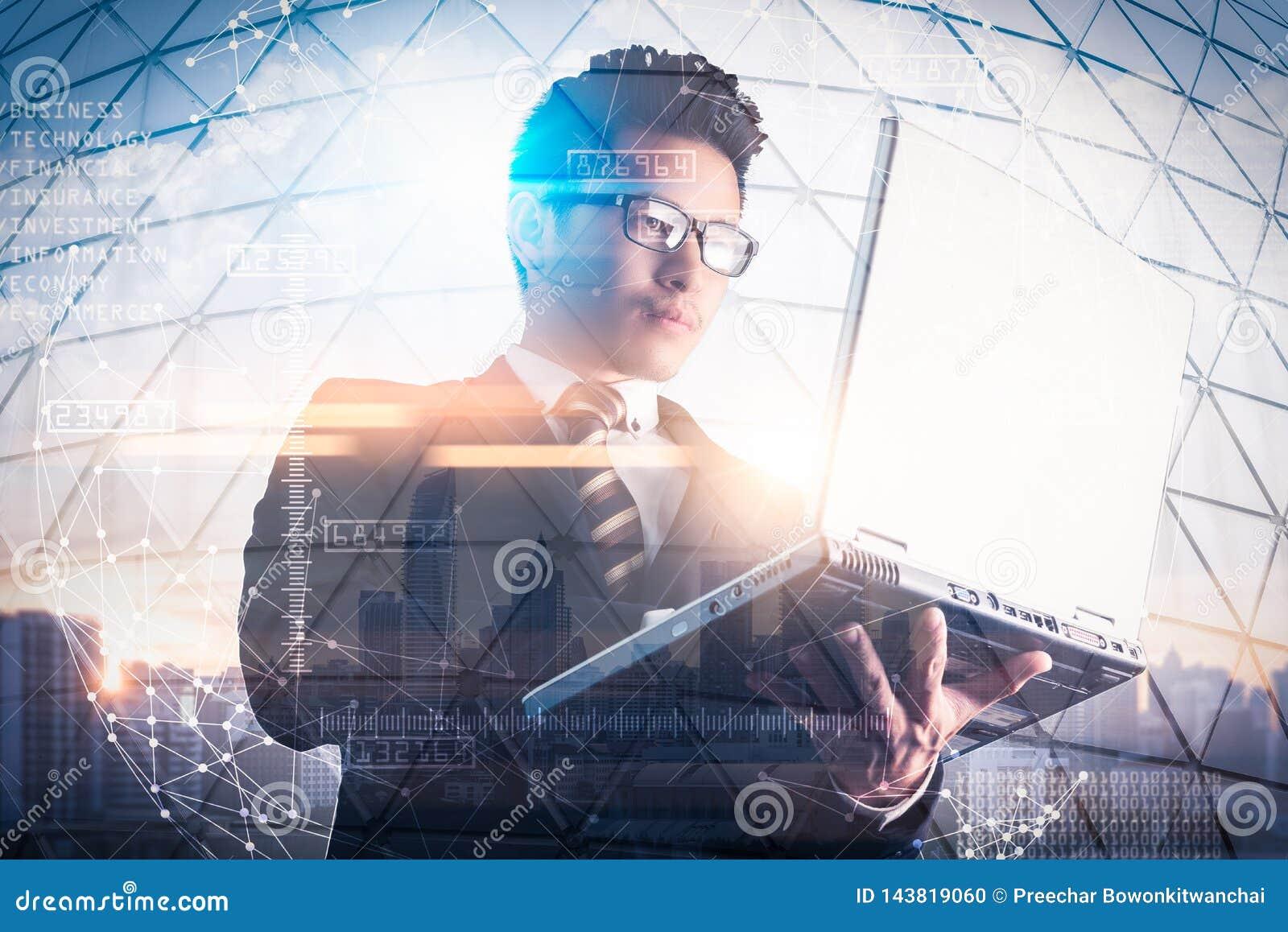 A imagem da exposição dobro do homem de negócios que usa um laptop durante o nascer do sol overlay com imagem da arquitetura da c