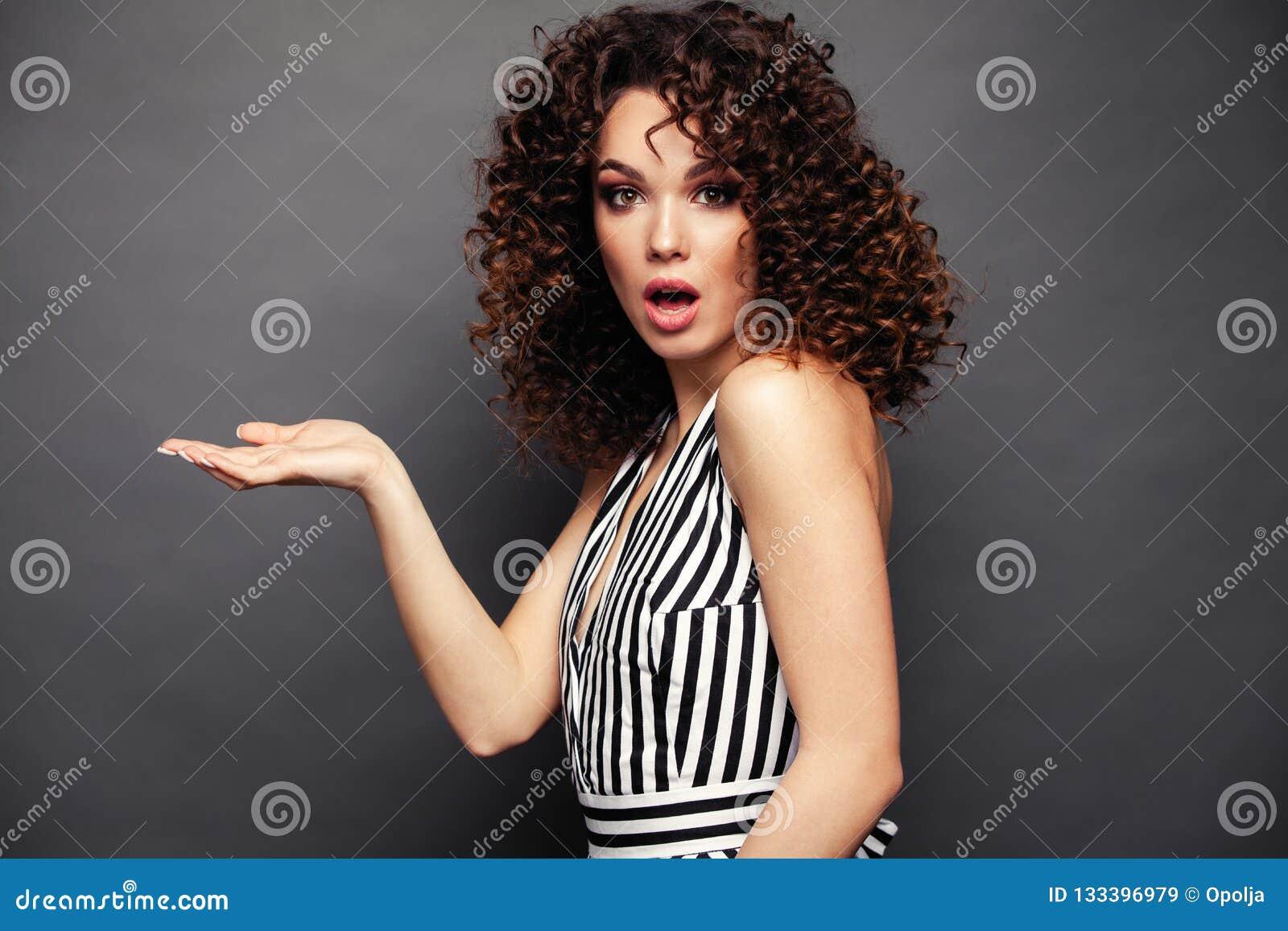 A imagem da jovem senhora feliz com afro ondula a posição do penteado isolada sobre o fundo cinzento Olhando apontar da câmera