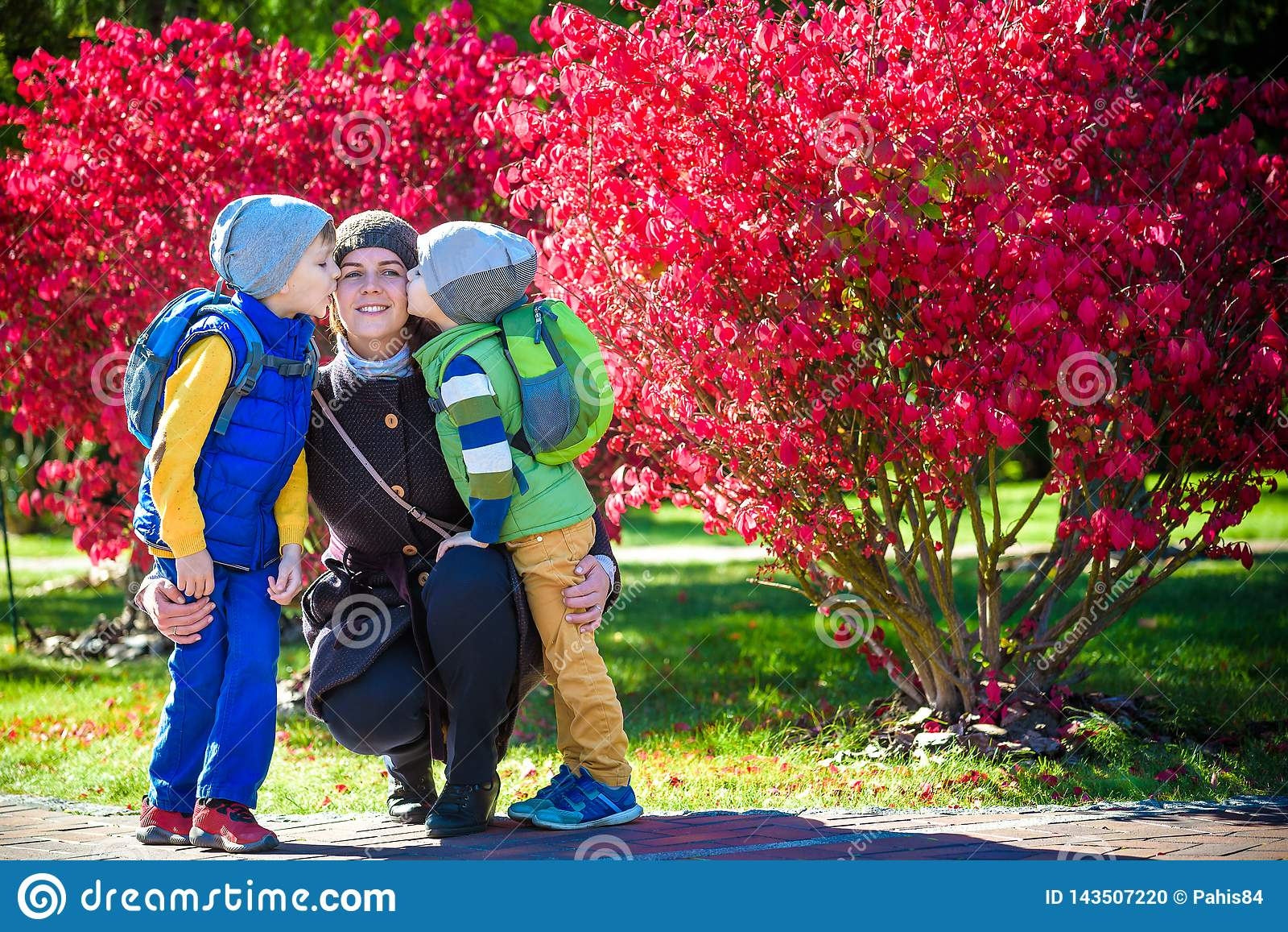 Imagem da mãe nova que abraça duas crianças pequenas, retrato do close up da família feliz, fêmea moreno bonito com o filho dois