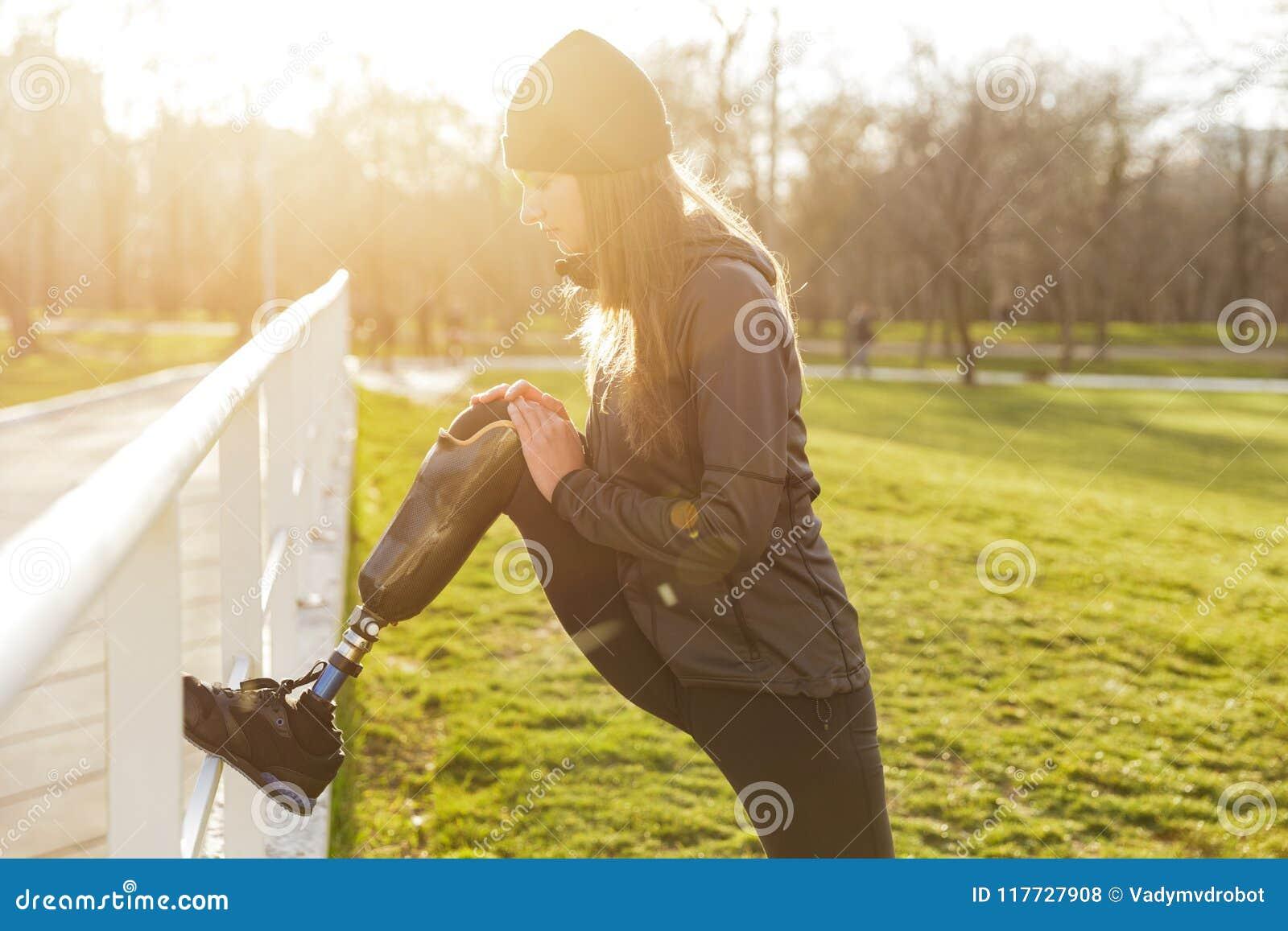 Imagem da menina atlética dos enfermos no sportswear, fazendo esportes e