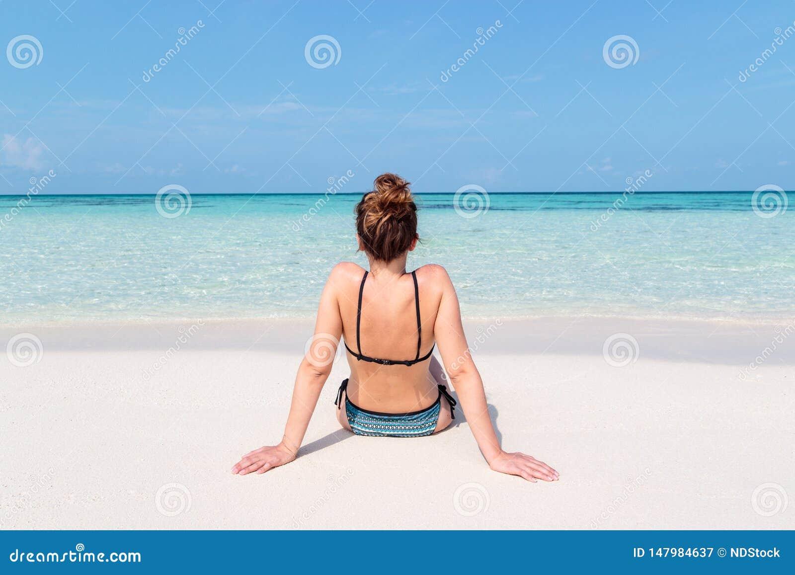 Imagem da parte traseira de uma jovem mulher assentada em uma praia branca em Maldivas ?gua azul claro como o fundo