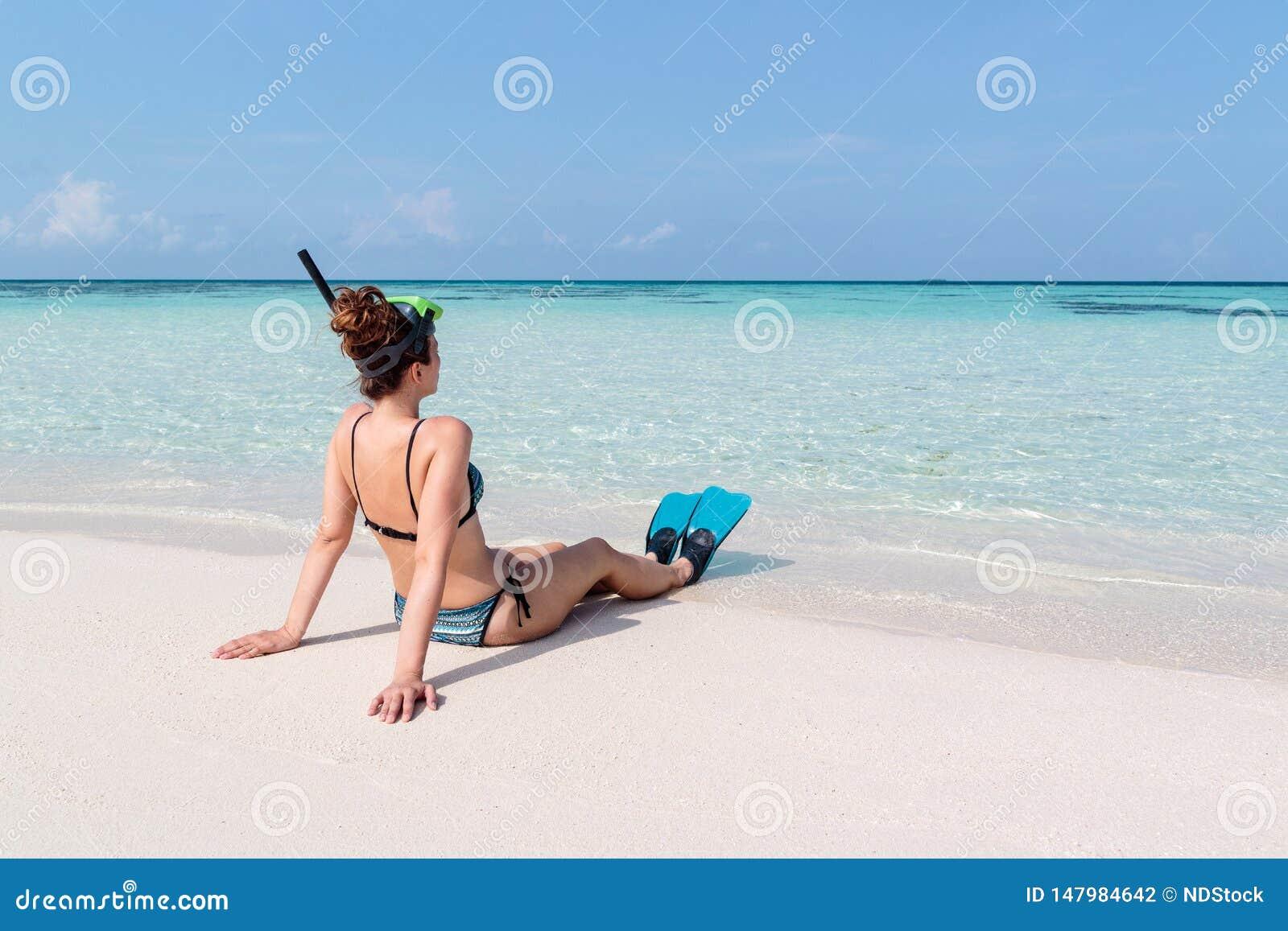 Imagem da parte traseira de uma jovem mulher com aletas e da máscara assentada em uma praia branca em Maldivas Água azul claro co