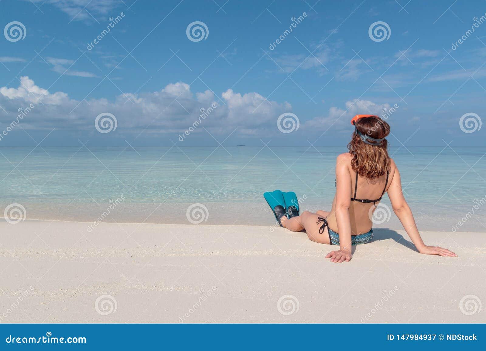 Imagem da parte traseira de uma jovem mulher com aletas e da m?scara assentada em uma praia branca em Maldivas ?gua azul claro co