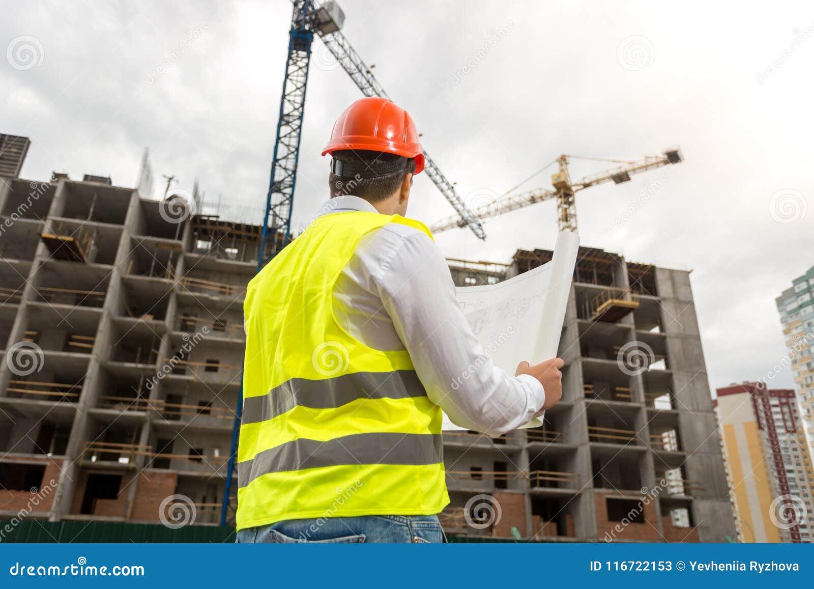 A imagem da vista traseira do arquiteto masculino no capacete de segurança e na veste que olham a construção de funcionamento cra