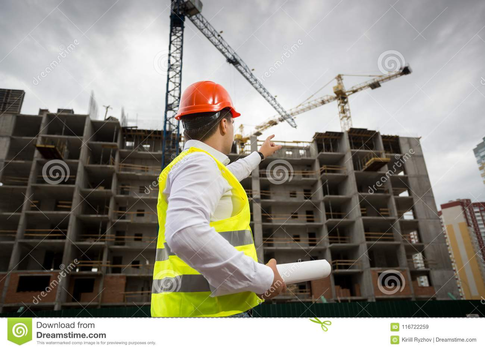 Imagem da vista traseira do arquiteto masculino no capacete de segurança que aponta na construção nova sob a construção
