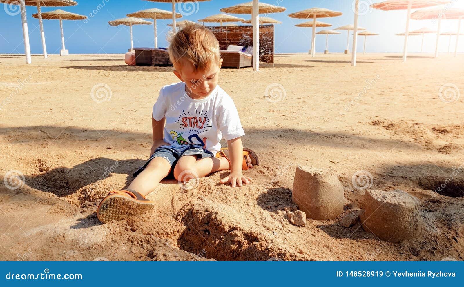 Imagem de 3 anos de menino pequeno idoso da crian?a que senta-se na praia do mar e no castelo de constru??o da areia molhada