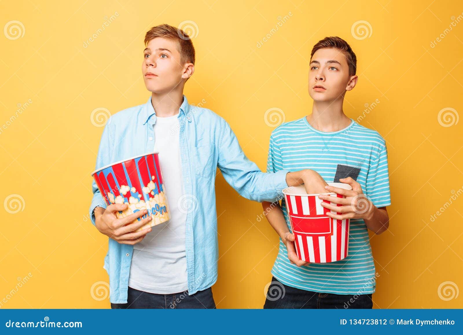 A imagem de dois excitou adolescentes bonitos, indivíduos que olham um filme interessante e que comem a pipoca em um fundo amarel