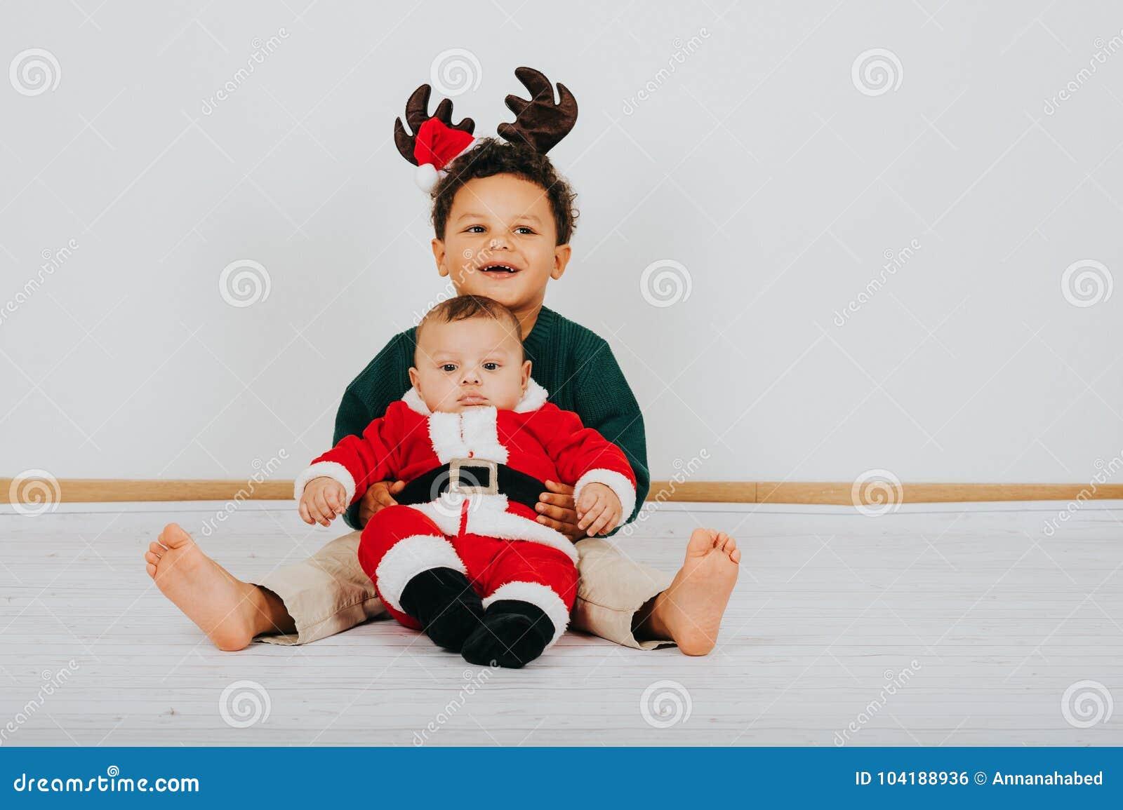 Imagem de dois meninos engraçados que vestem o equipamento do Natal
