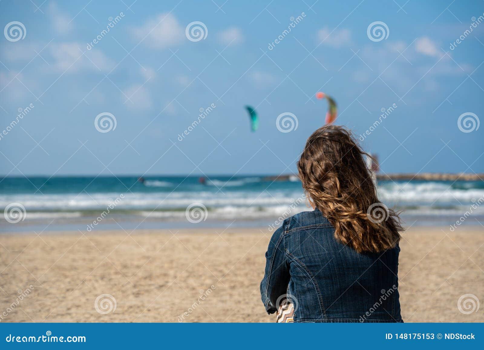 Imagem de uma mulher na praia que olha dois kitesurfers no mar