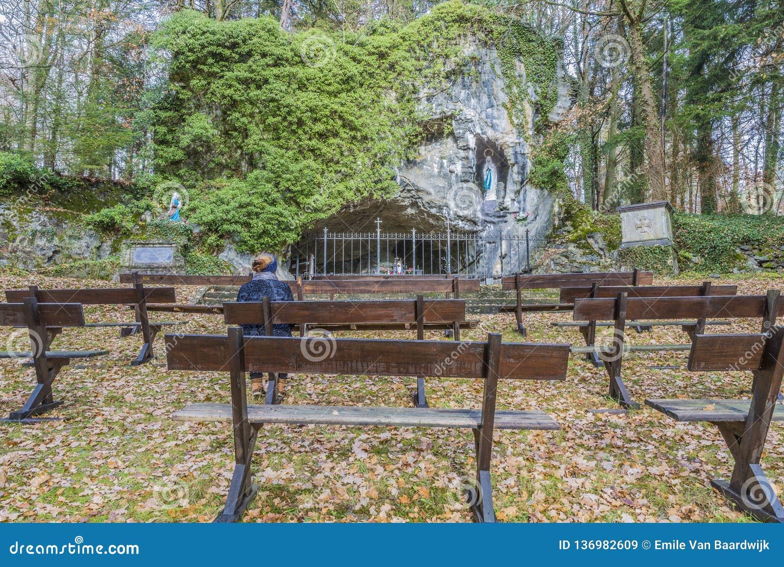 Imagem de uma mulher que senta-se em um banco que reza fora ao Virgin de Lourdes