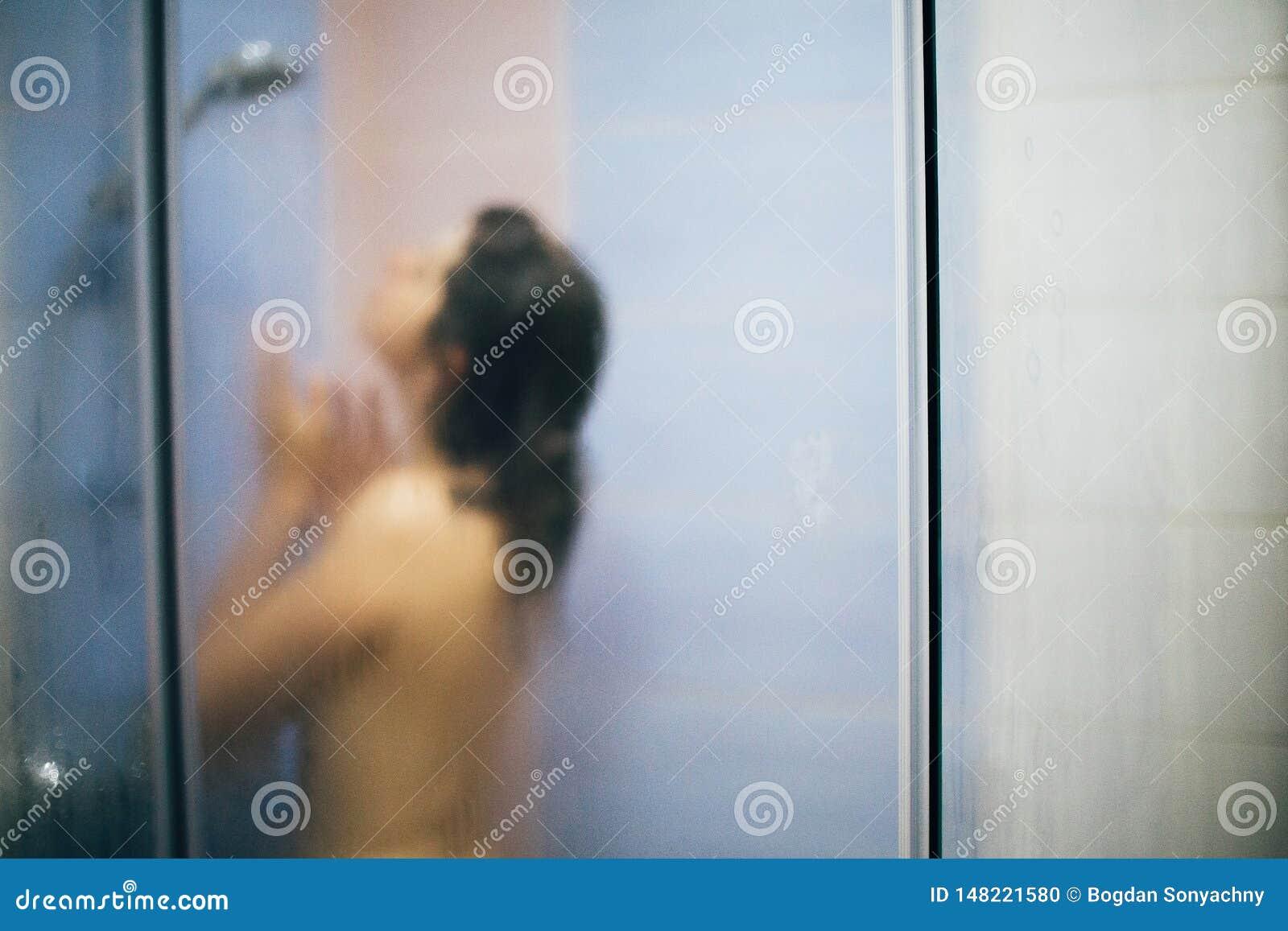 Imagem defocused borrada da mulher feliz que toma o chuveiro quente em casa ou o banheiro do hotel Menina moreno bonita que aprec