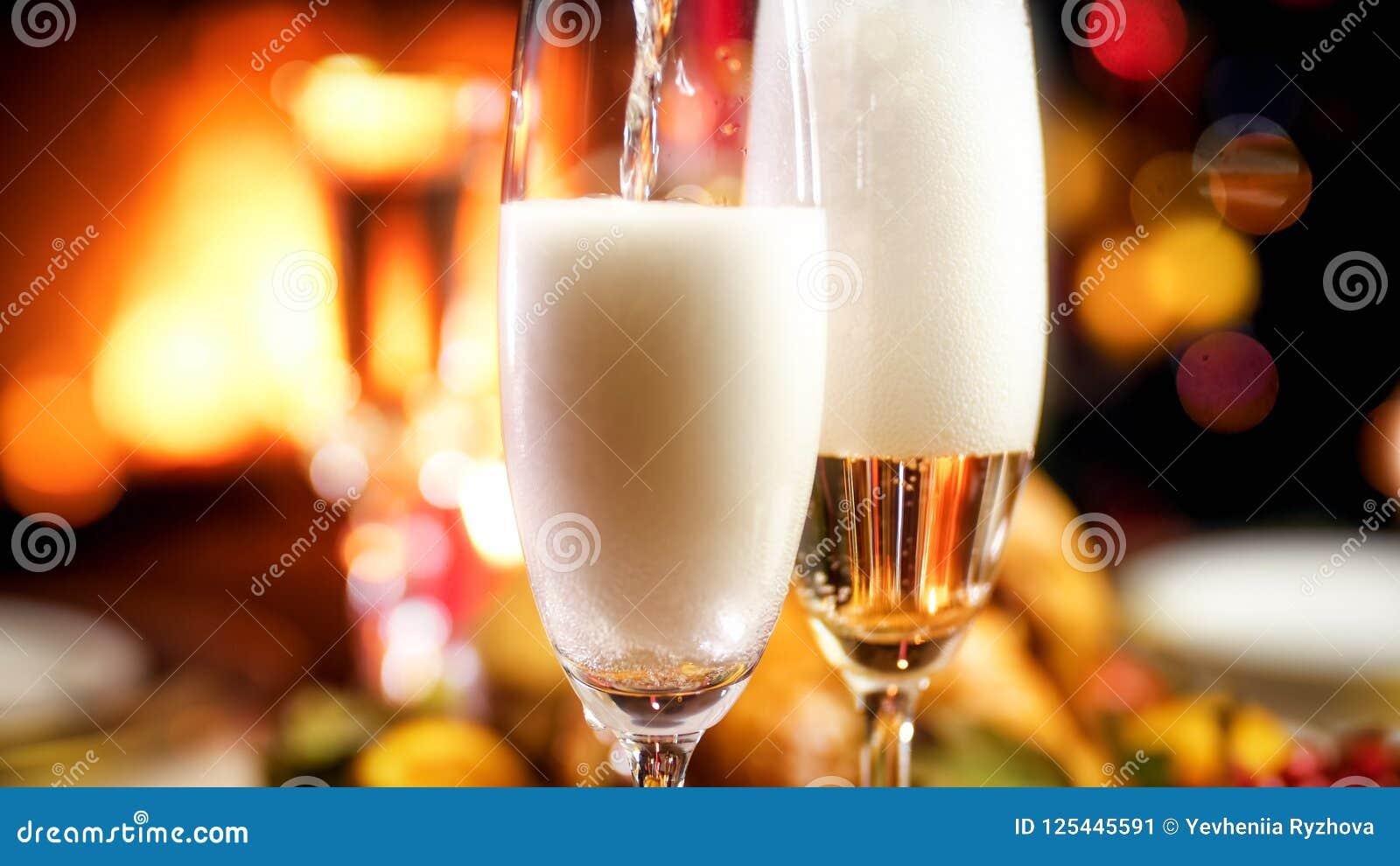 Imagem do close up do champanhe de derramamento nos vidros no jantar de Natal romântico