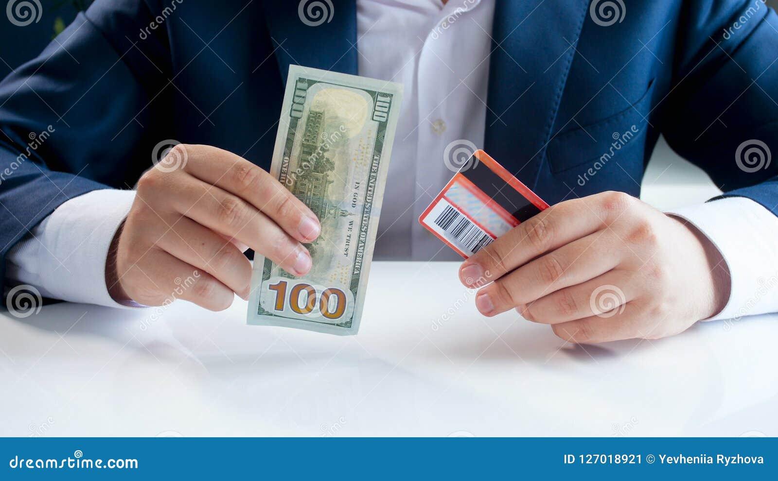 Imagem do close up da dúvida do homem de negócios de usar o cartão de crédito ou cédulas tradicionais do papel moeda