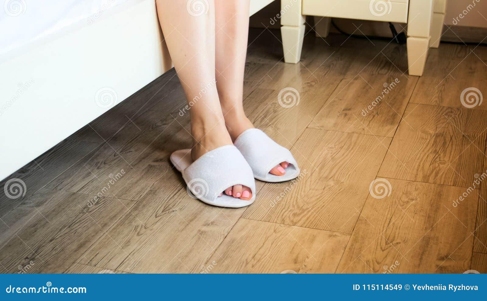 Imagem do close up dos pés fêmeas que vestem os deslizadores brancos do hotel na cama