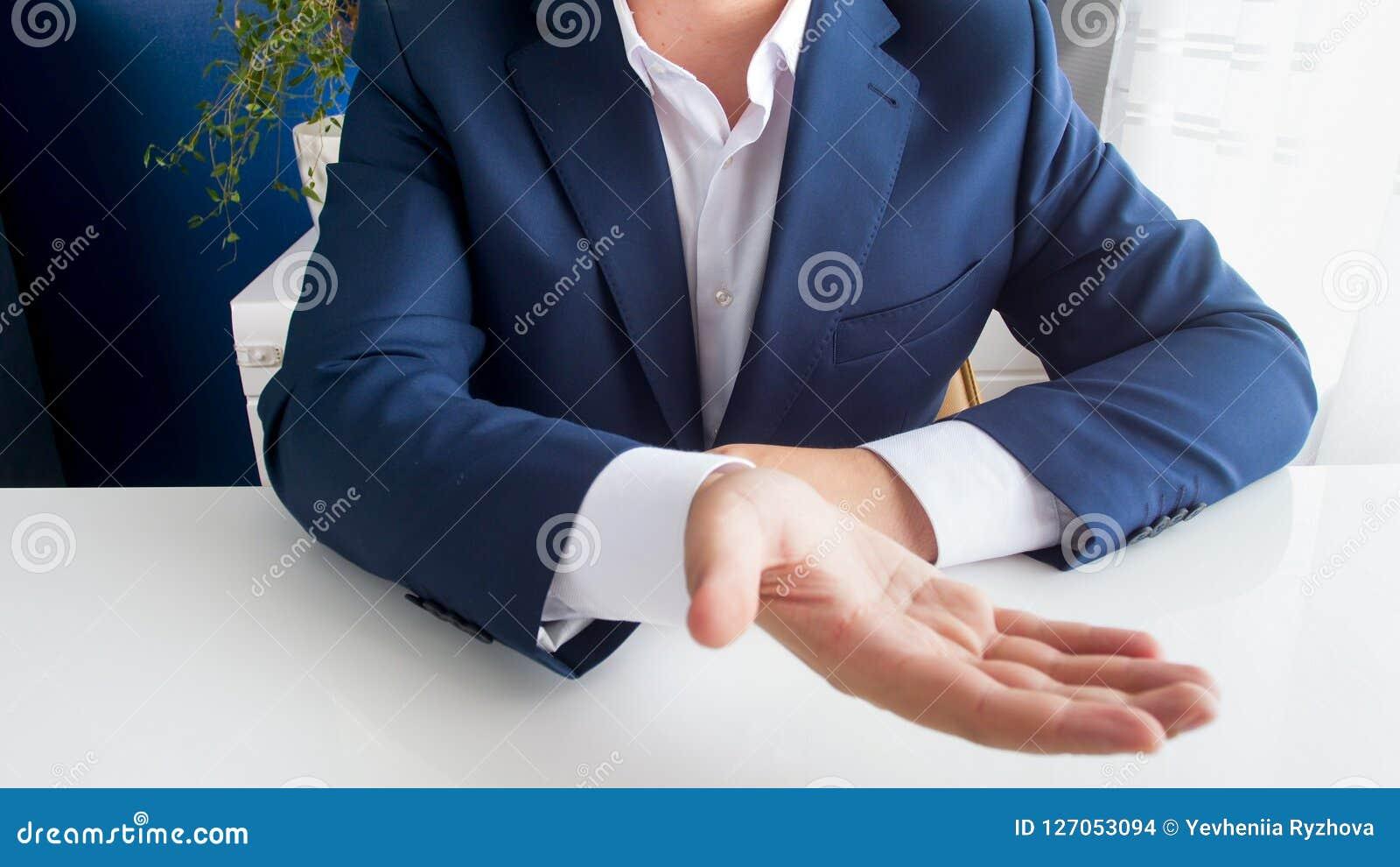 Imagem do close up do homem de negócios que senta-se atrás da mesa de escritório que estica a mão e que pede o dinheiro