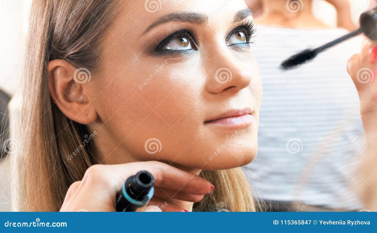 Imagem do close up do maquilhador que aplica o rímel com escova