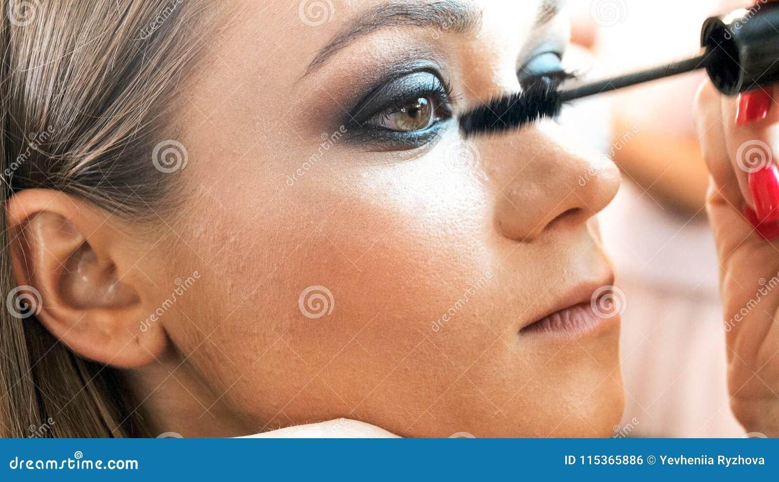 A imagem do close up do maquilhador que aplica o smokey eyes a composição