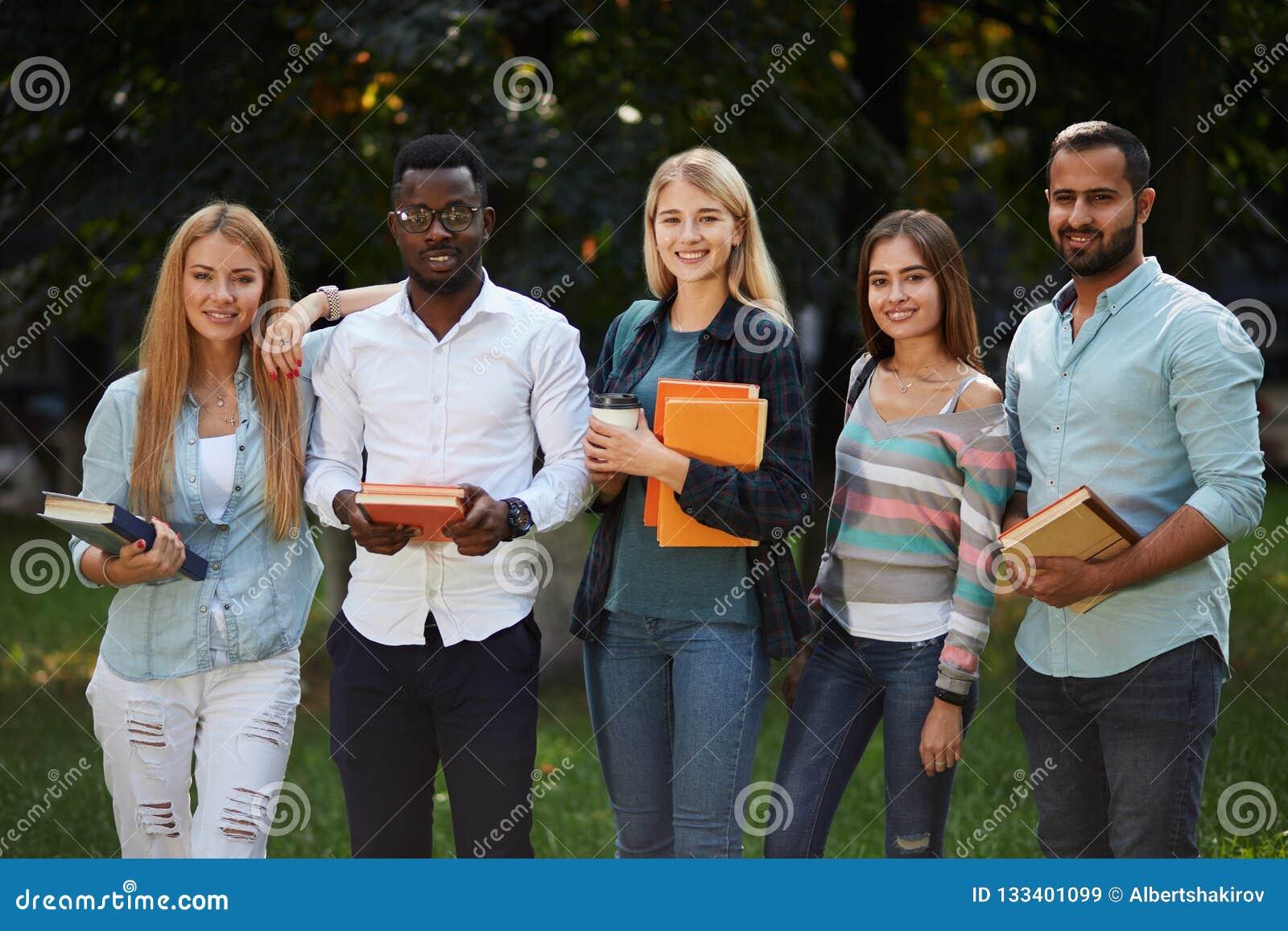 Imagem do grupo multi-étnico de estudantes de graduados que estão fora