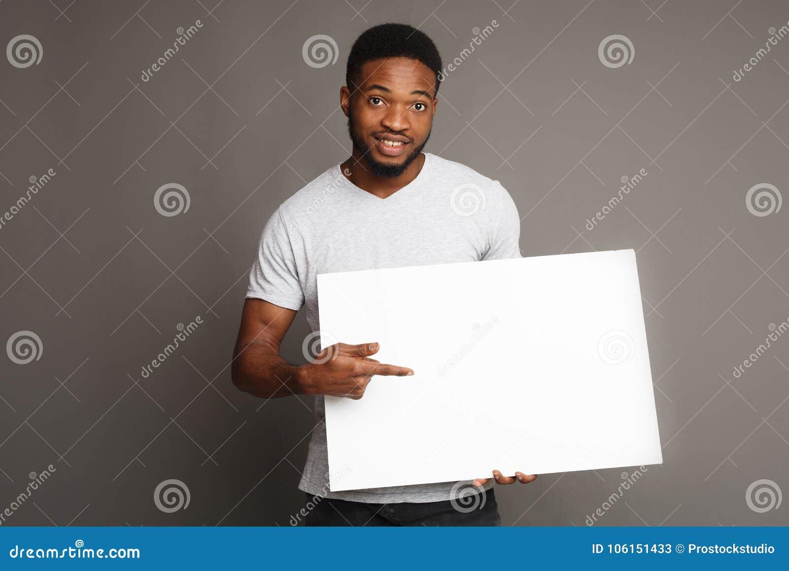 Imagem do homem afro-americano novo que guarda a placa vazia branca