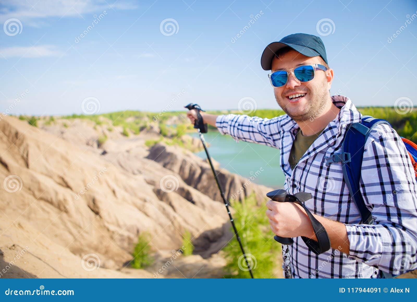 Imagem do homem alegre do turista com a trouxa que estica para a frente com as varas para andar no monte