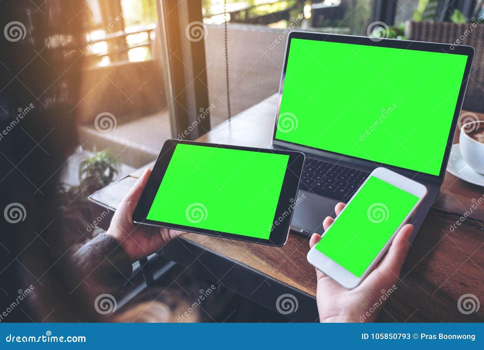 Imagem do modelo de uma mulher de negócios que guarda o telefone celular branco, a tabuleta preta e o portátil com a tela verde v