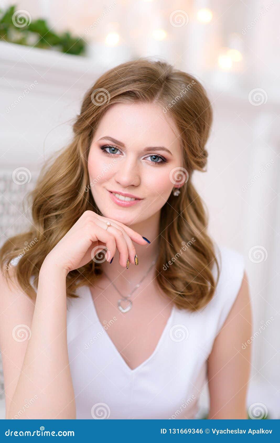 Imagem do retrato de uma menina bonita nova e natural que olha com seu relance encantador e suave em linha reta na câmera