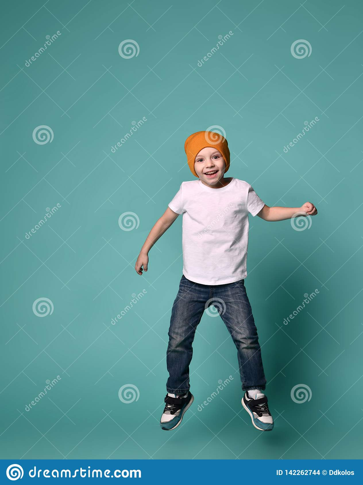Imagem do salto da criança do rapaz pequeno isolado sobre o fundo verde