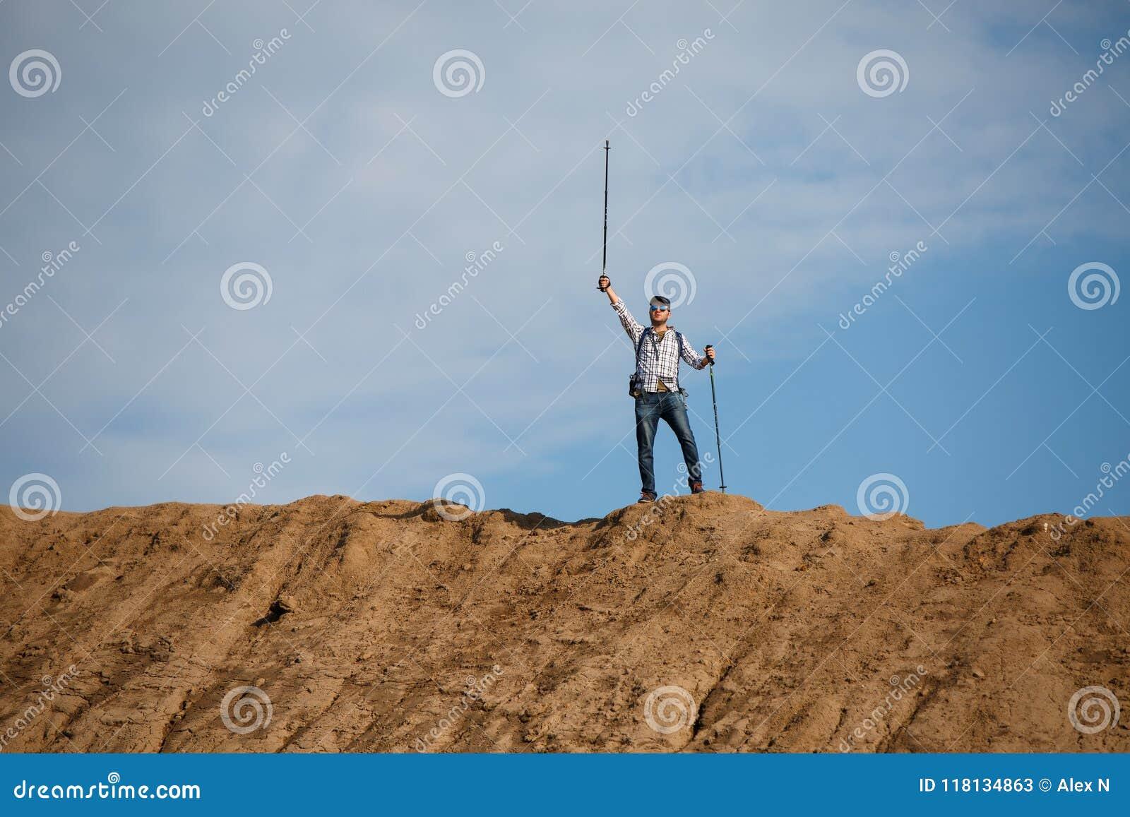 Imagem do turista do homem de longe com mãos acima com as varas para andar no monte