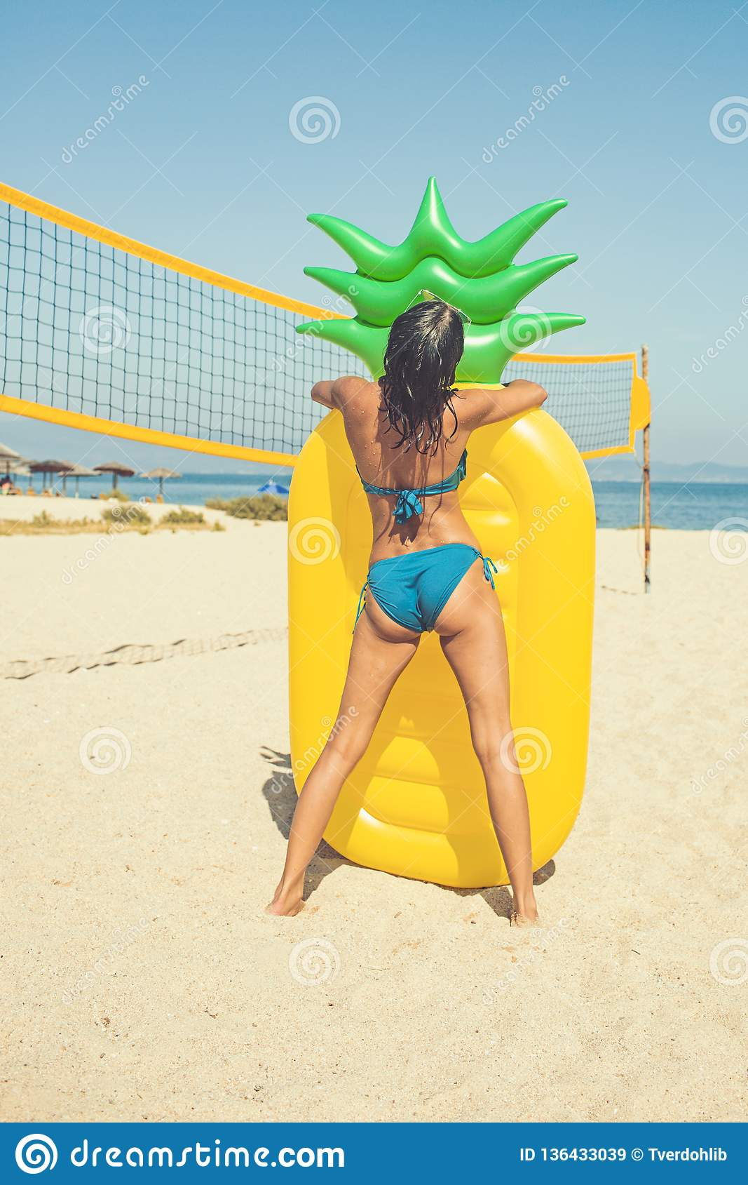 Imagem do verão da menina suntanned impressionante no colchão inflável amarelo do abacaxi na corte de voleibol