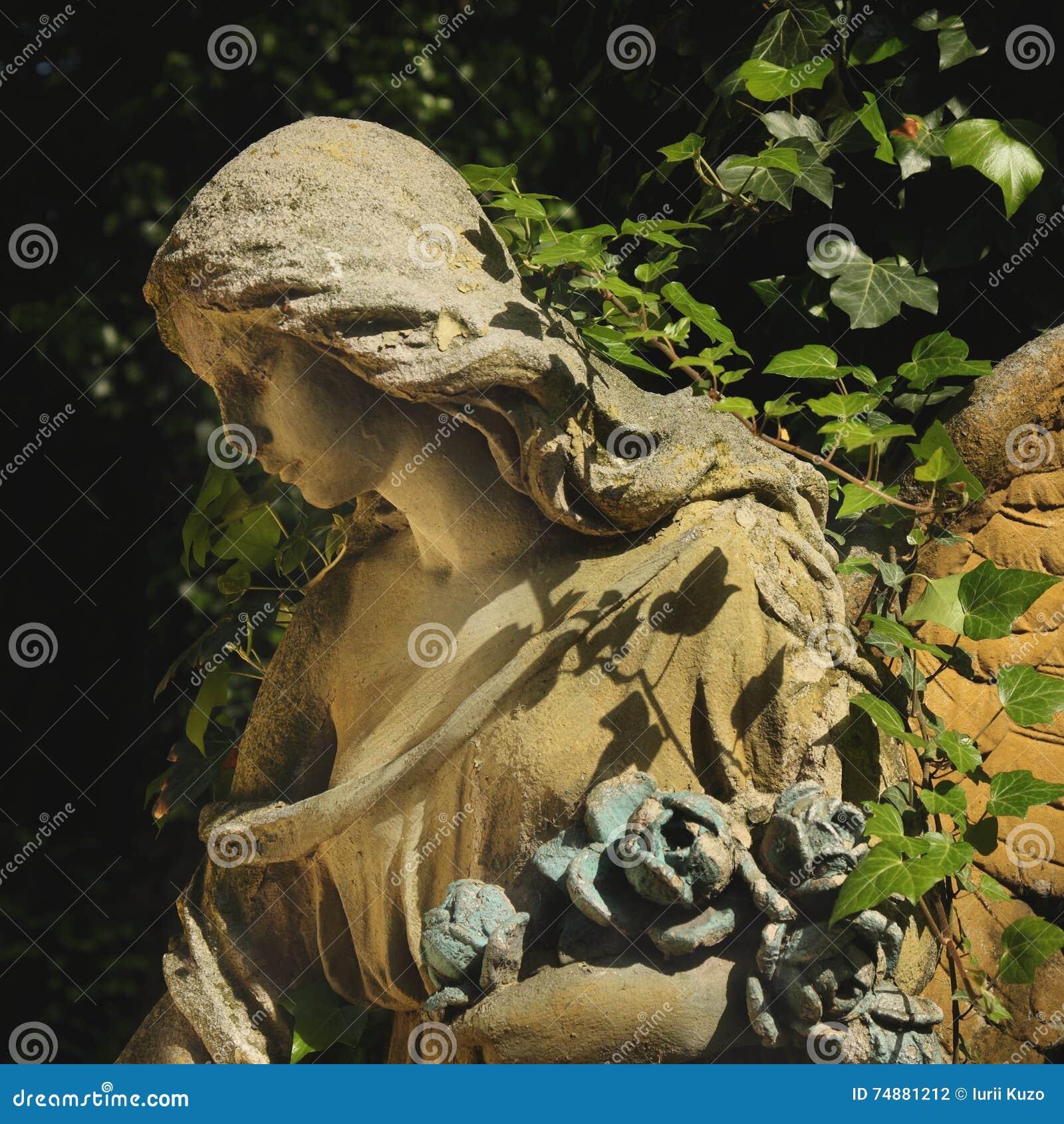 Imagem do vintage de um anjo triste em um cemitério contra o backgroun