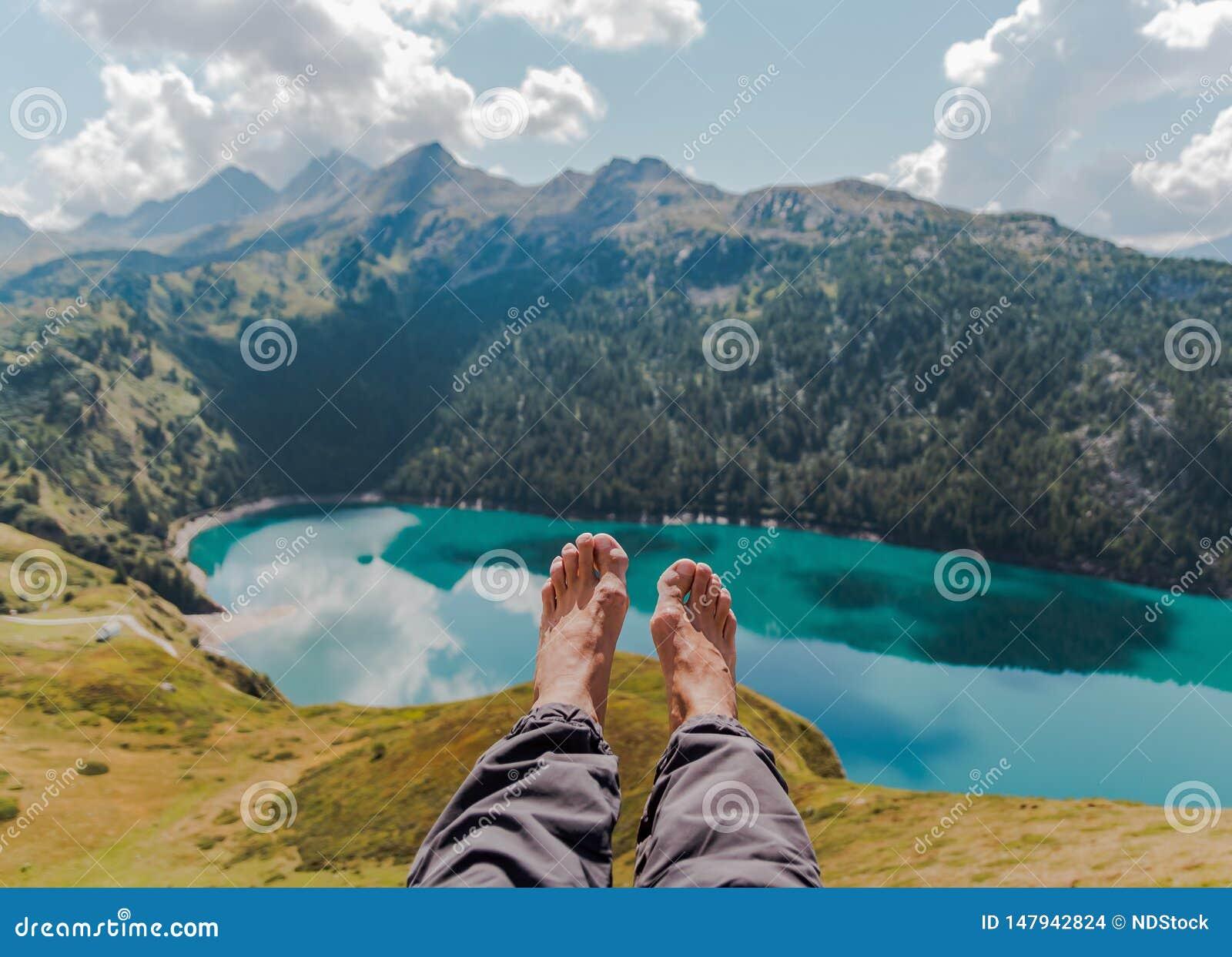 Imagem dos pés e dos pés com montanhas e do lago masculinos de Ritom como um fundo