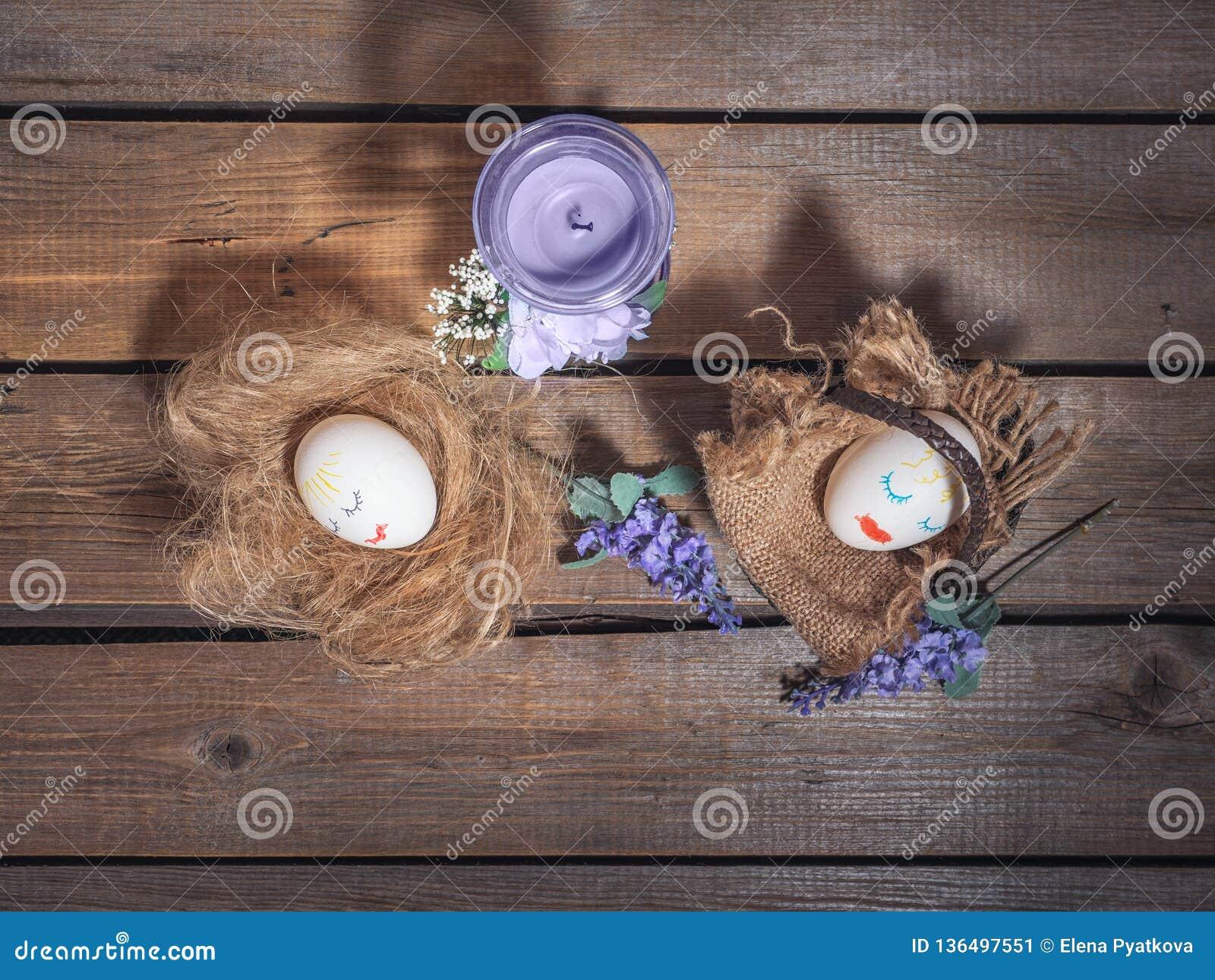 Imagem engraçada para a Páscoa Ovos com caras pintadas A cesta e a palha, são em seguida ramos das flores em um fundo de madeira