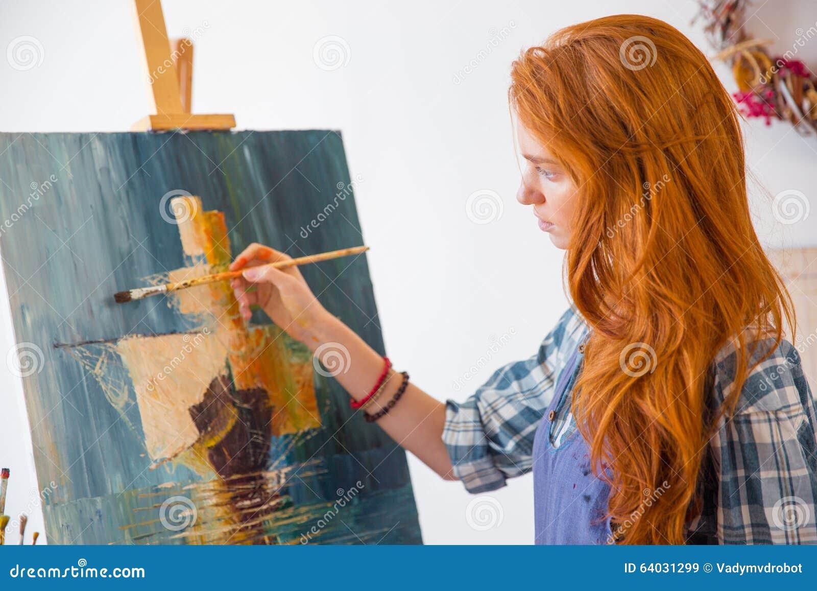 Imagem fêmea nova sereno bonita da pintura do pintor na oficina da arte