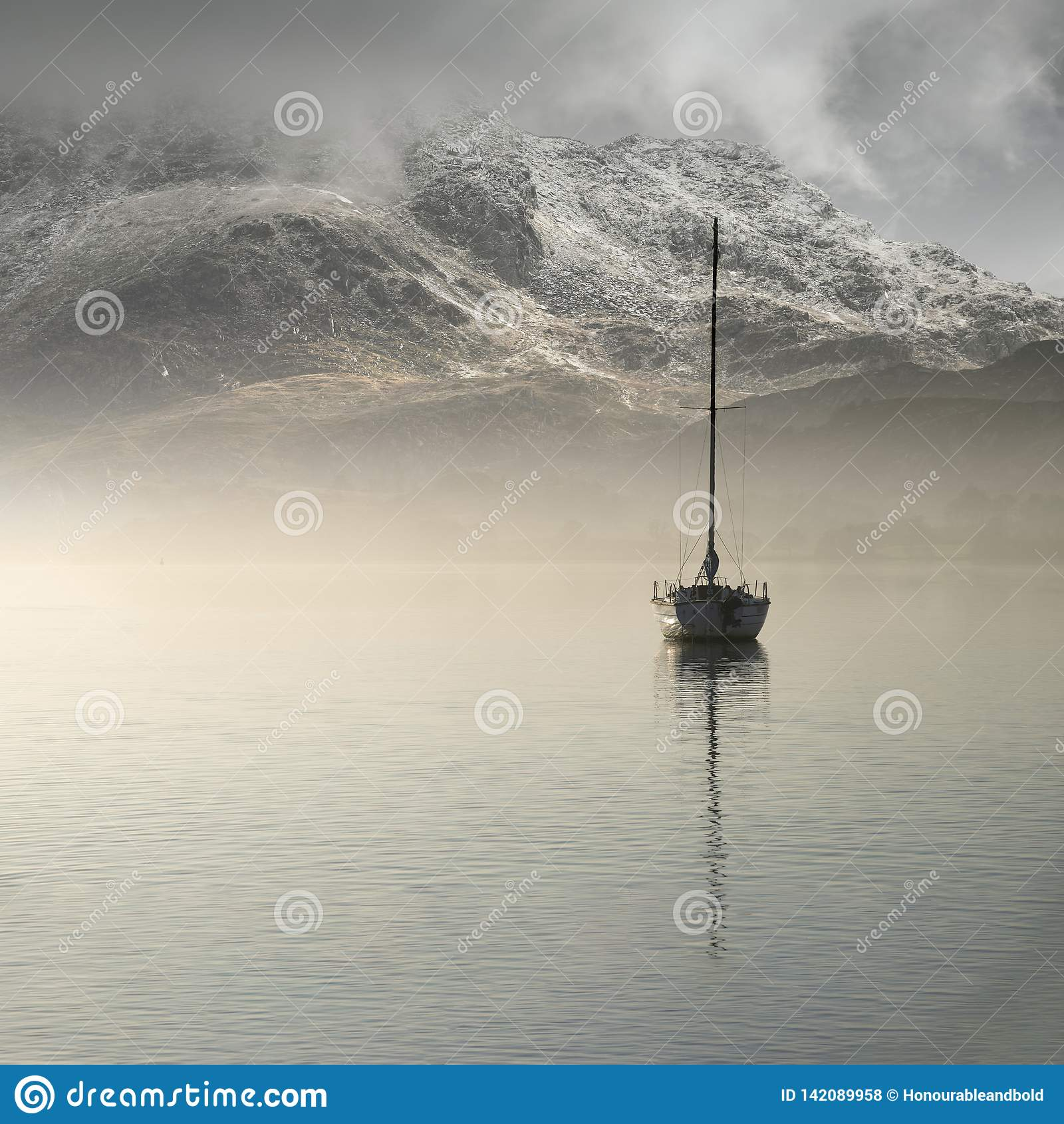 Imagem impressionante da paisagem de navegar o iate que senta-se ainda na água calma do lago com a montanha que aparece no fundo