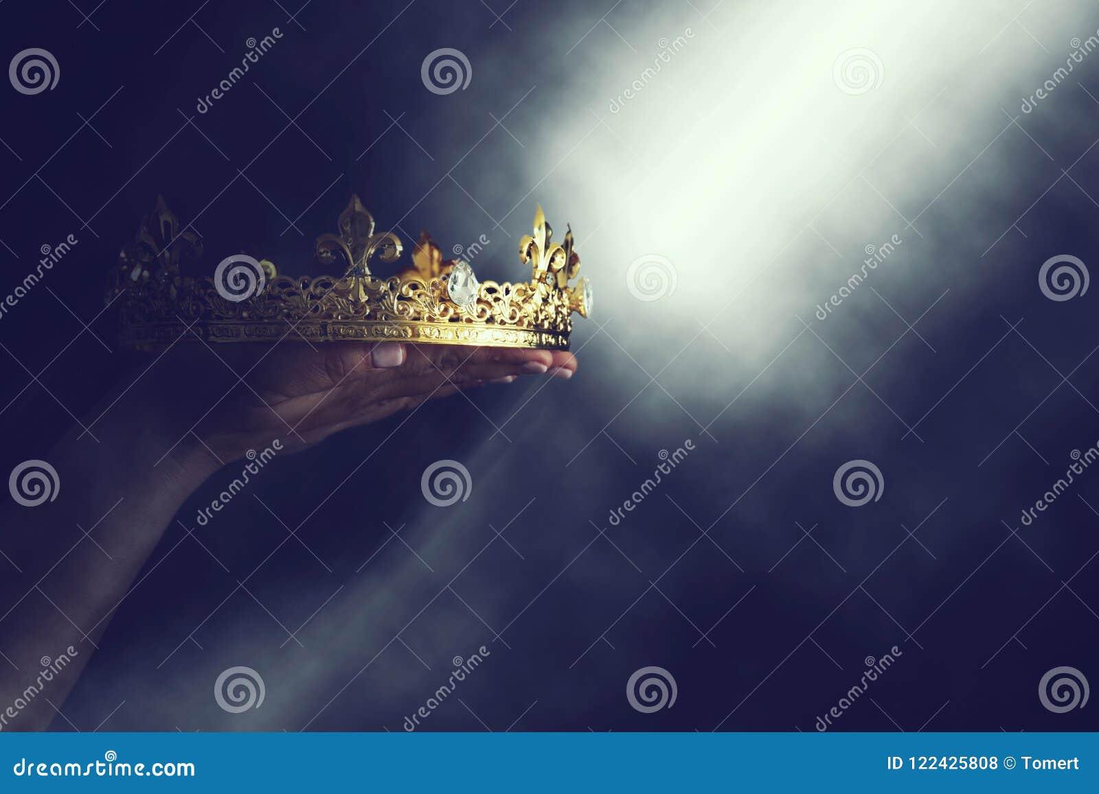 Imagem mágica de Mysteriousand da mão do ` s da mulher que guarda uma coroa do ouro sobre o fundo preto gótico conceito medieval