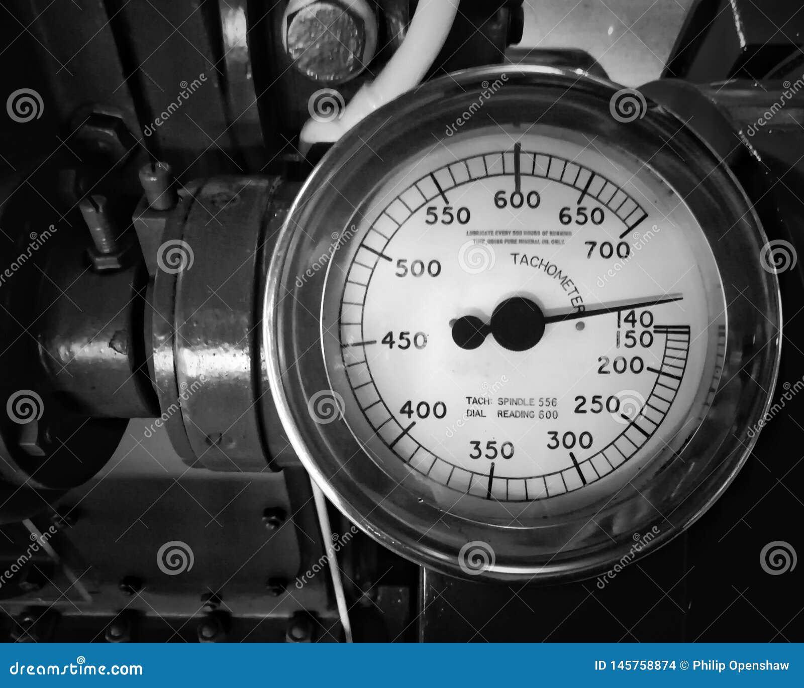 Imagem monocromática de um grande tacômetro velho do metal com um calibre redondo com o seletor marcado nos números montados em u