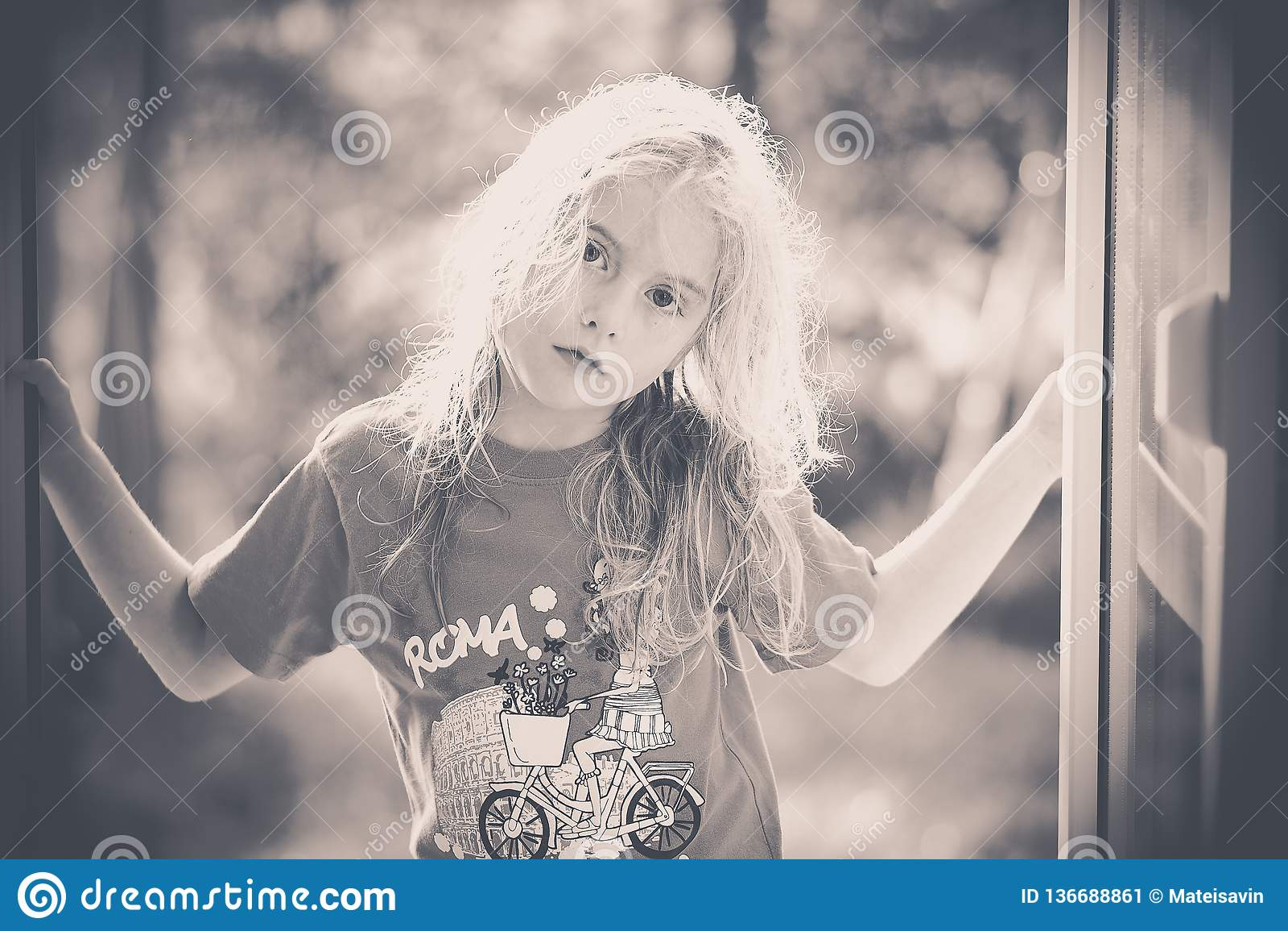 Imagem preto e branco de uma menina loura que olha me