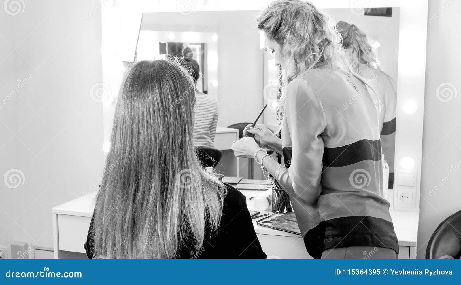 Imagem preto e branco do maquilhador que aplica a composição no estúdio da cara