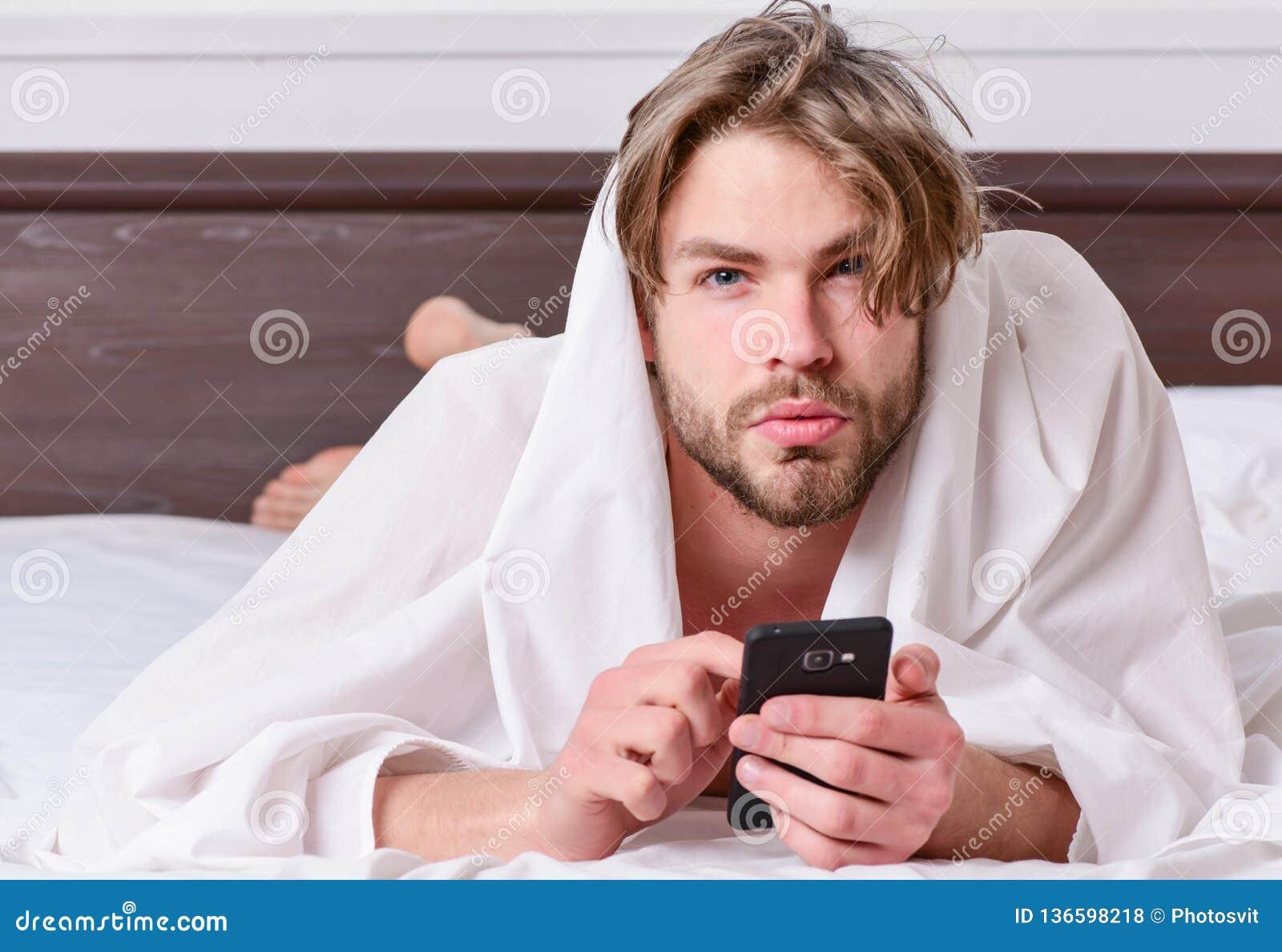 Imagem que mostra o homem novo que estica na cama Pés do homem que dormem na cama confortável Acorde a manhã