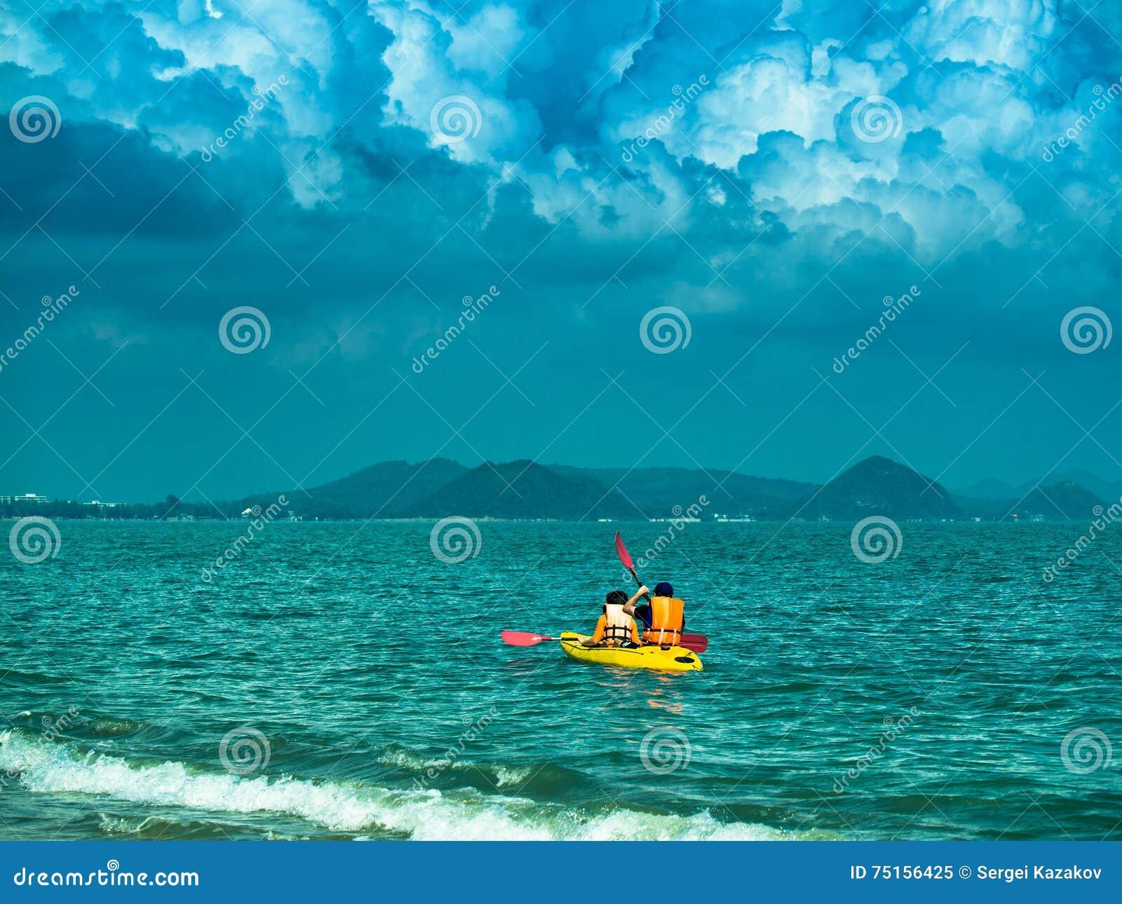 A imagem tonificada de um caiaque amarelo com dois turistas navega no mar no fundo do céu dramático