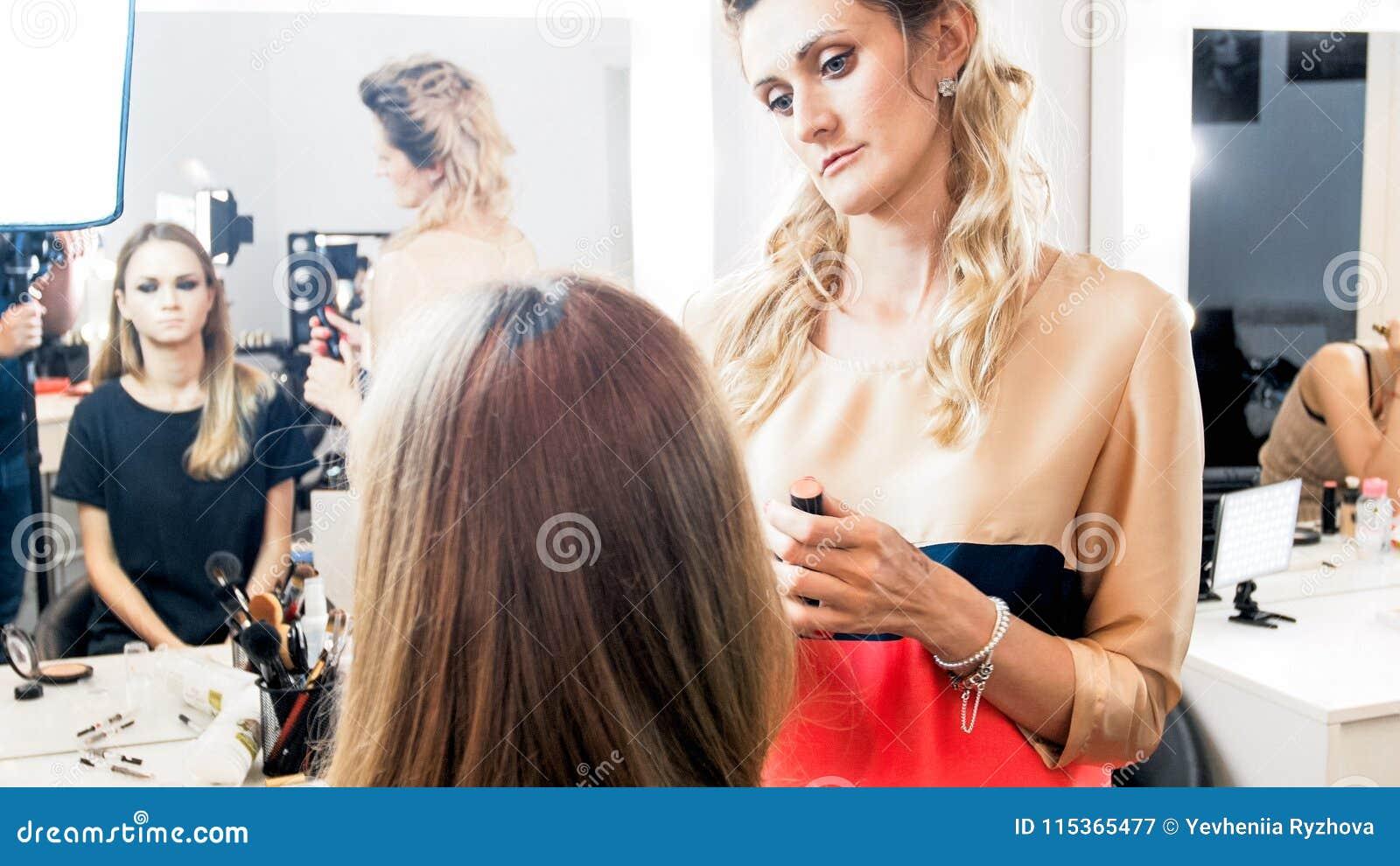 Imagem tonificada do maquilhador profissional que trabalha com modelo no estúdio da beleza