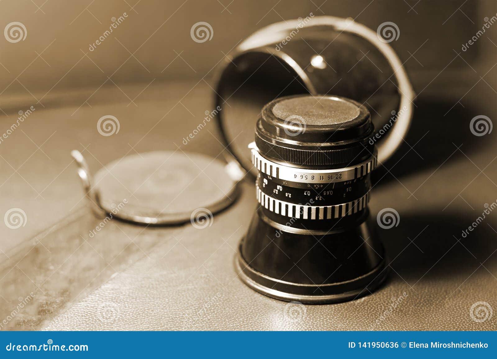 Imagen ascendente cercana de la lente polvorienta del viejo vintage con la caja en el fondo borroso, foco selectivo