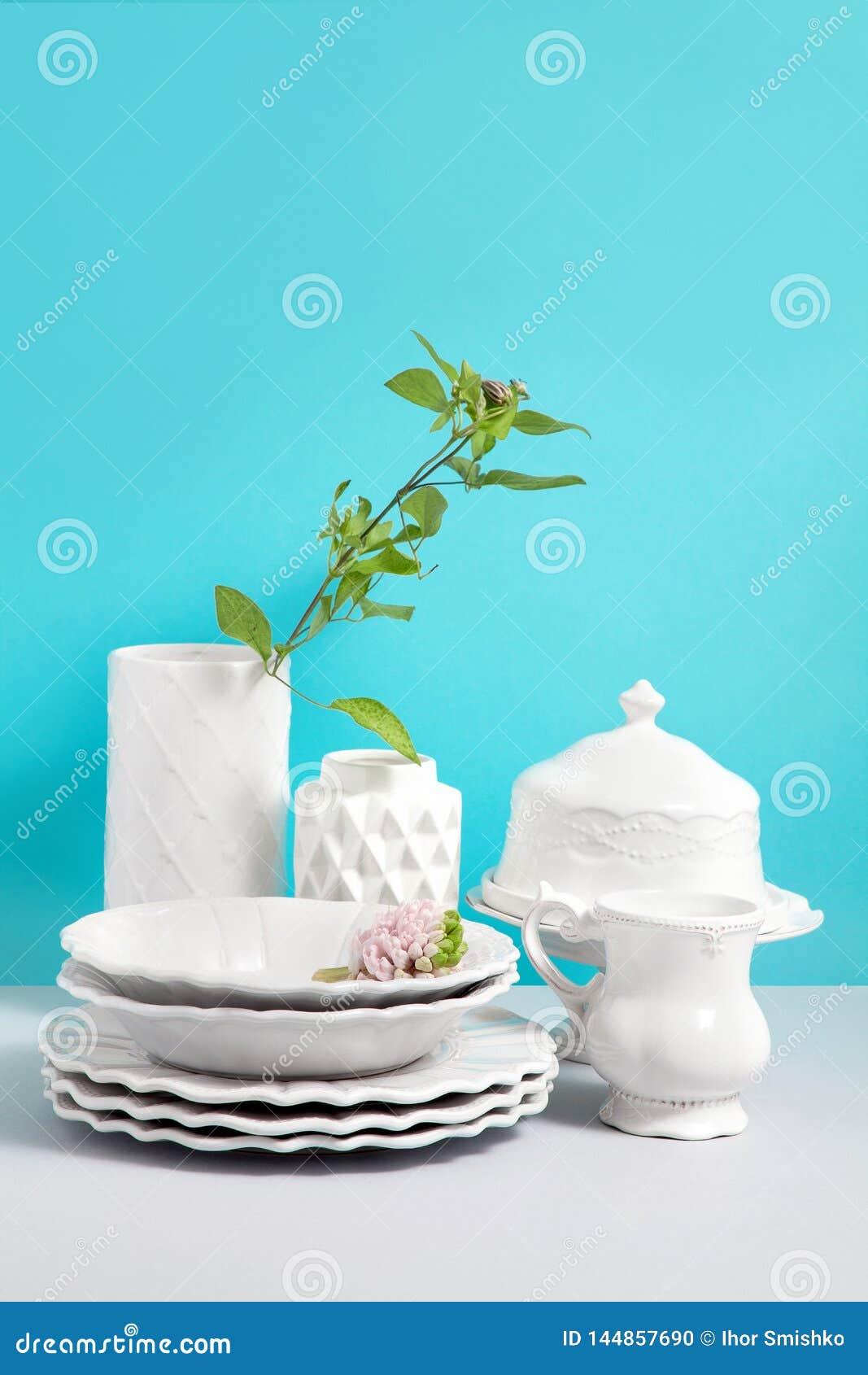 Imagen ascendente falsa con la loza, el plato, los utensilios y los floreros blancos en la tabla gris contra fondo azul con el es