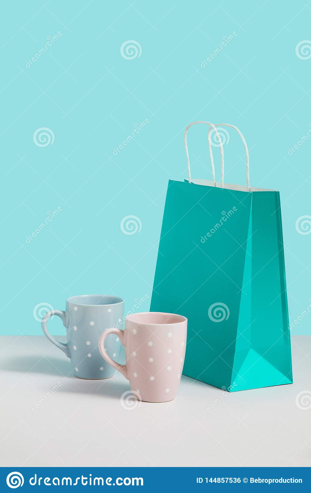 Imagen ascendente falsa con tender las tazas del t? cerca del soporte de la bolsa de papel en fondo azul Imagen del concepto del