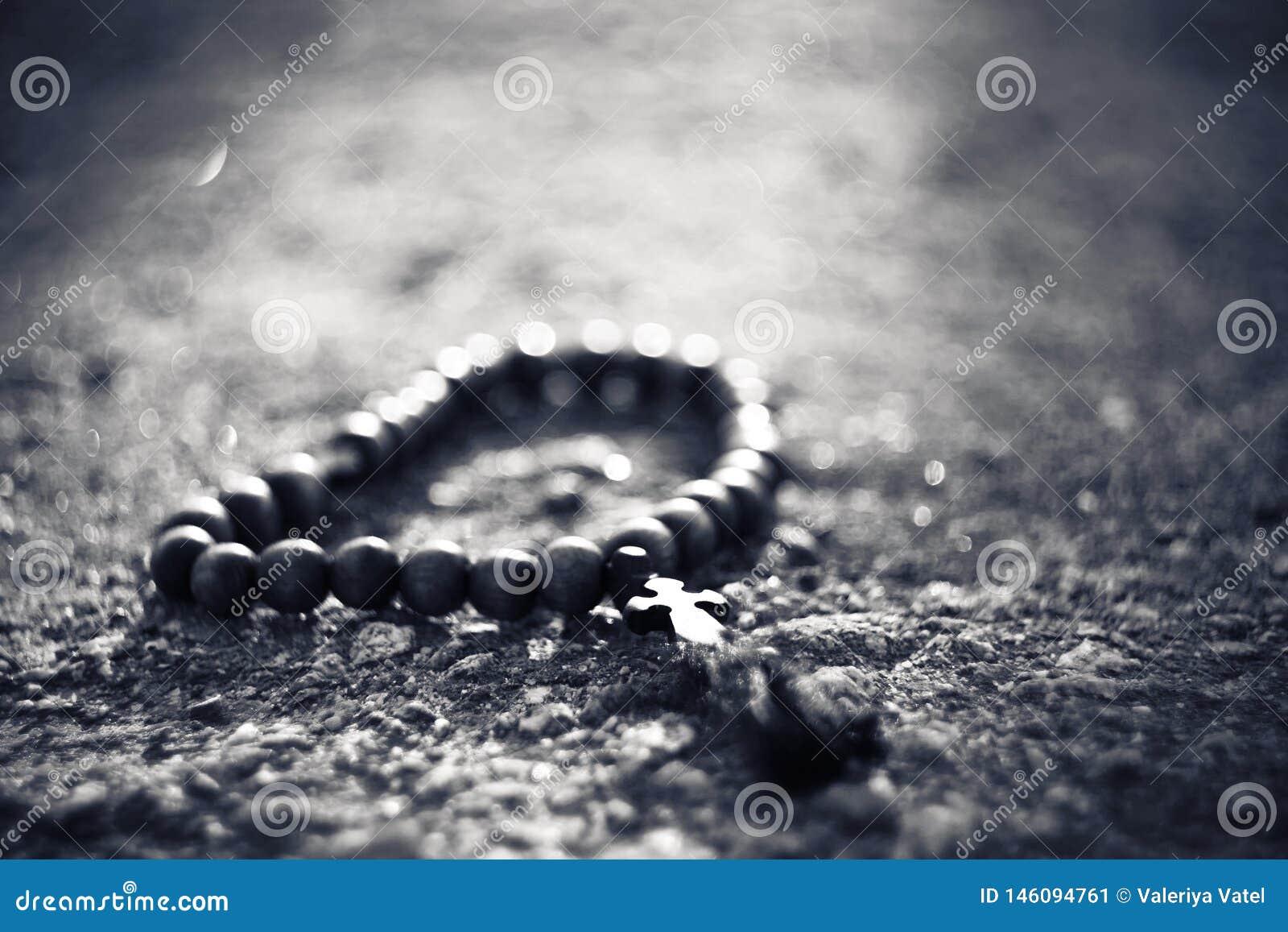 Imagen blanco y negro del rosario de madera con una cruz