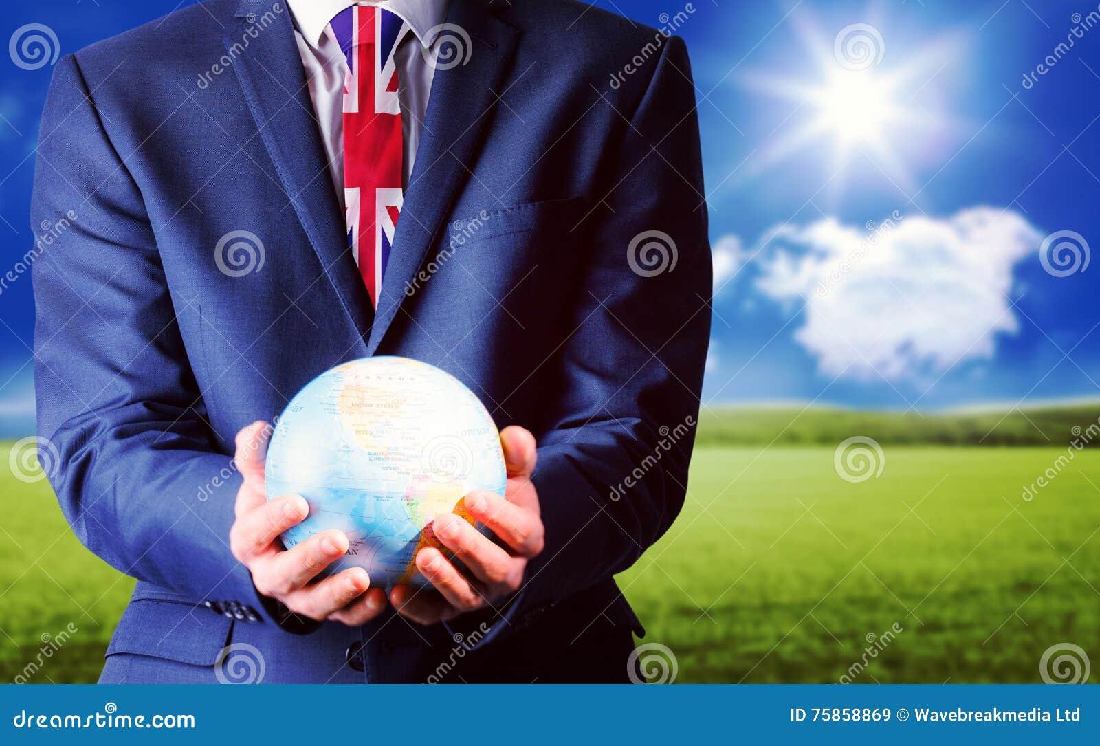 Imagen compuesta de la mano del hombre de negocios que sostiene el globo terrestre