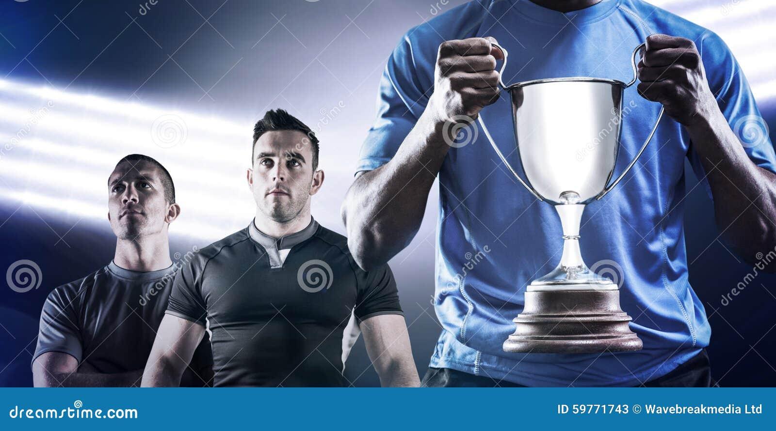 Imagen compuesta de la mediados de sección del deportista que sostiene el trofeo